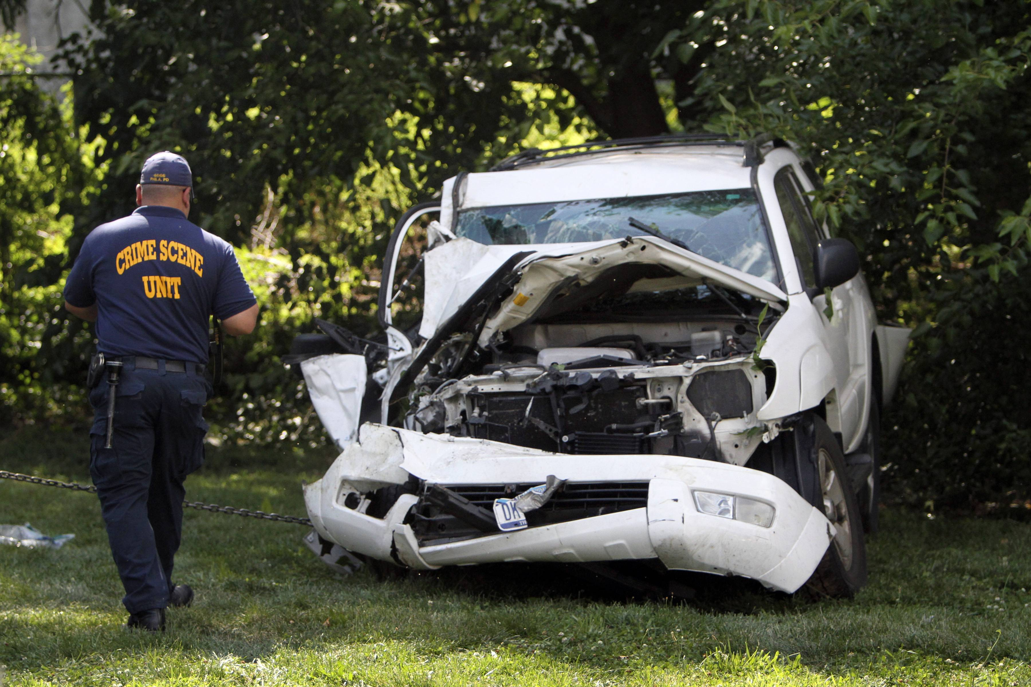 An investigator examines a heavily damaged SUV before it is towed from the scene of a fatal accident in North Philadelphia, Friday July 25. Two children were killed and three people critically injured when a hijacked car lost control and hit a group of people near a fruit stand, according to police.