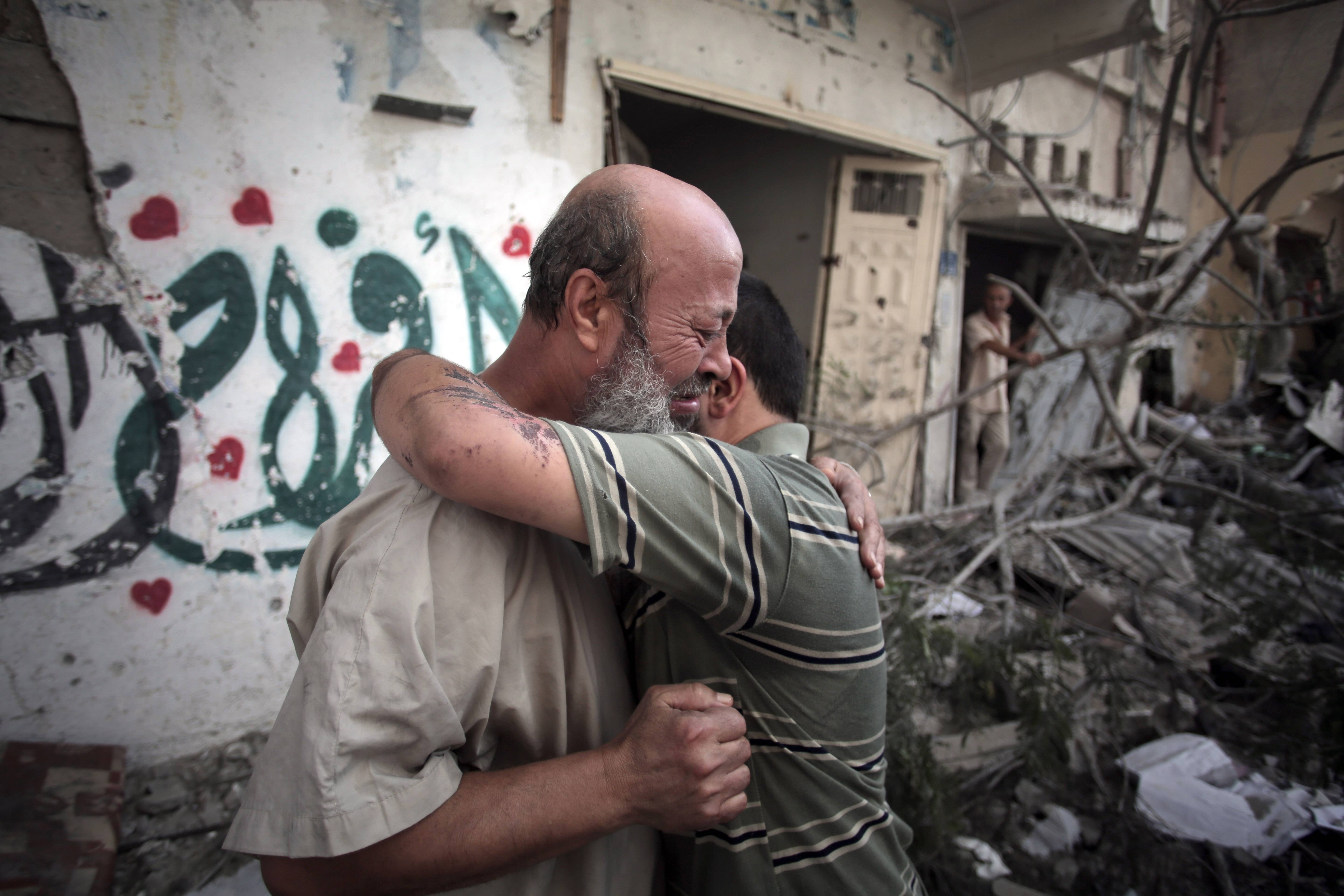 Palestinians hug each other after seeing their homes destroyed, during a 12-hour cease-fire in Gaza City's Shijaiyah neighborhood, Saturday, July 26. Gaza residents used a 12-hour humanitarian cease-fire on Saturday to stock up on supplies and survey the devastation from nearly three weeks of fighting, as they braced for a resumption of Israel's war on Hamas amid stalled efforts to secure a longer truce.