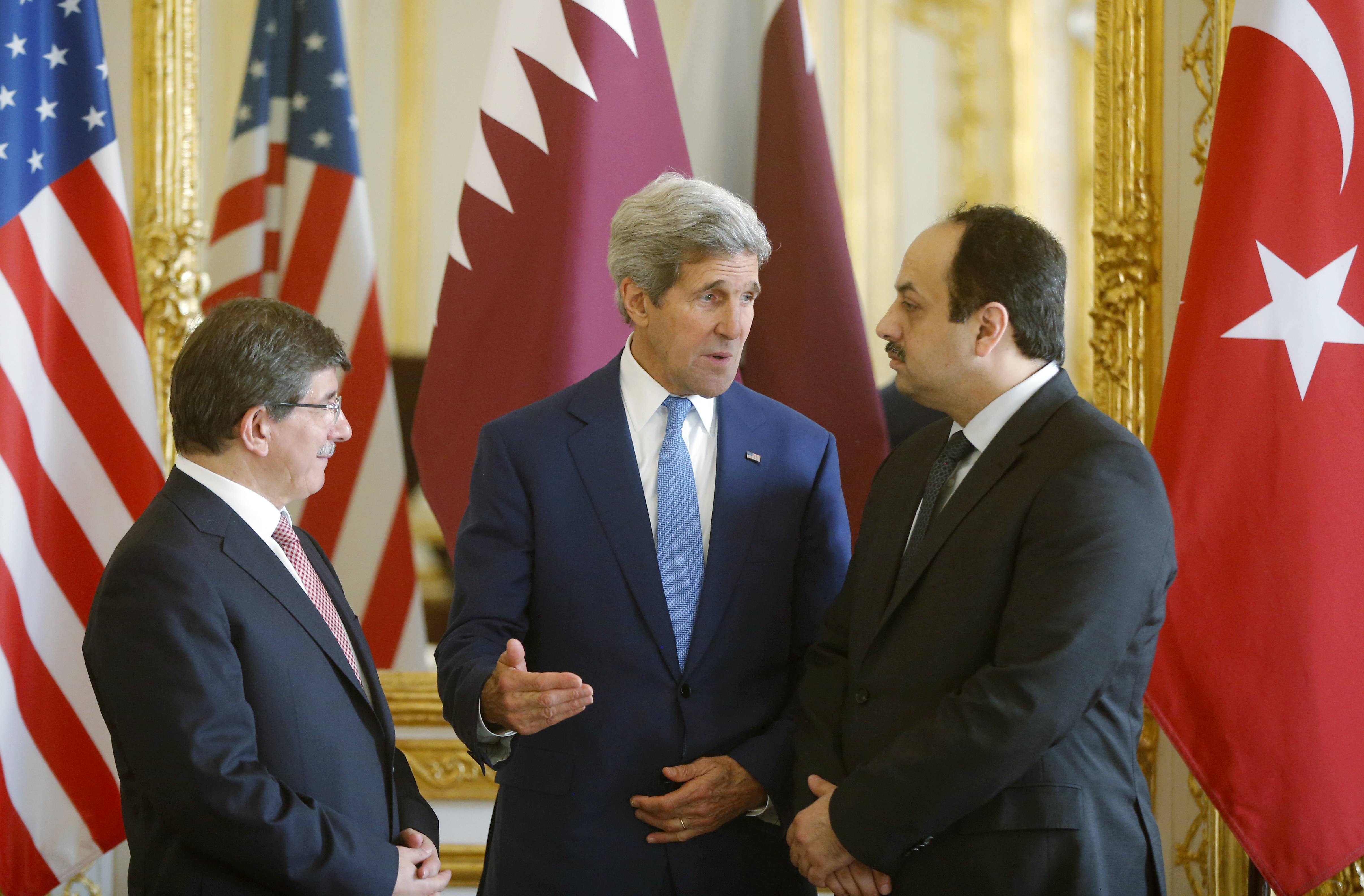 U.S. Secretary of State John Kerry, center, speaks with Qatari Foreign Minister Khaled al-Attiyah, right, and Turkish Foreign Minister Ahmet Davutoglu before they make statements to reporters during their meeting regarding a cease-fire between Hamas and Israel in Gaza, Saturday, July 26, at the U.S. ambassador's residence in Paris, France. With a 12-hour humanitarian cease-fire in Gaza Saturday, Kerry is continuing with efforts to reach a longer truce between Israel and Hamas.