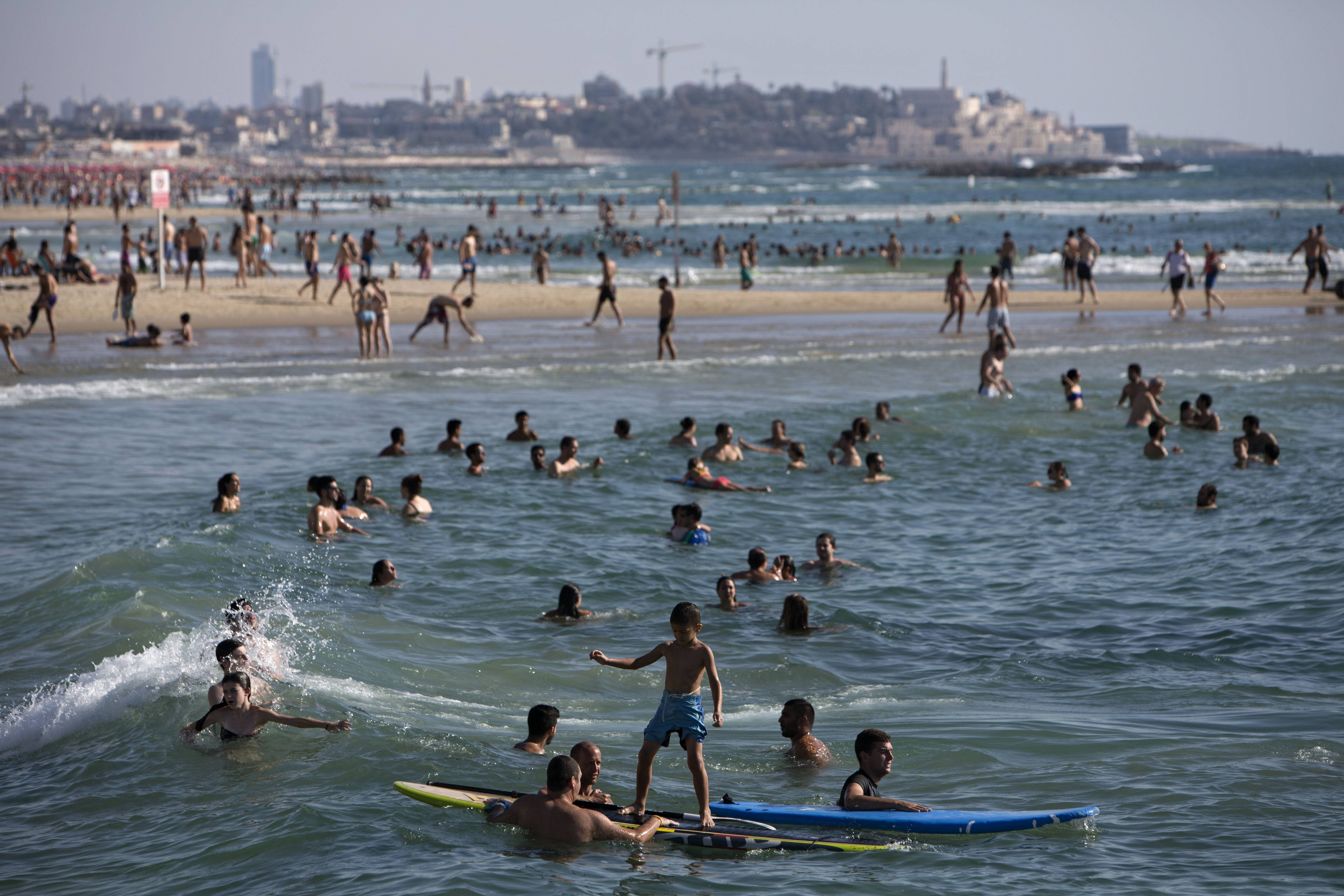 Israelis and tourists enjoy the Mediterranean Sea beachfront during a humanitarian cease-fire in the Gaza war, in Tel Aviv, Israel, Saturday, July 26. Israel agreed Saturday to extend a 12-hour humanitarian truce in the Gaza war by four hours, a Cabinet minister said. In Gaza, a health official said the Palestinian death toll in 19 days of fighting had surpassed 1,000.