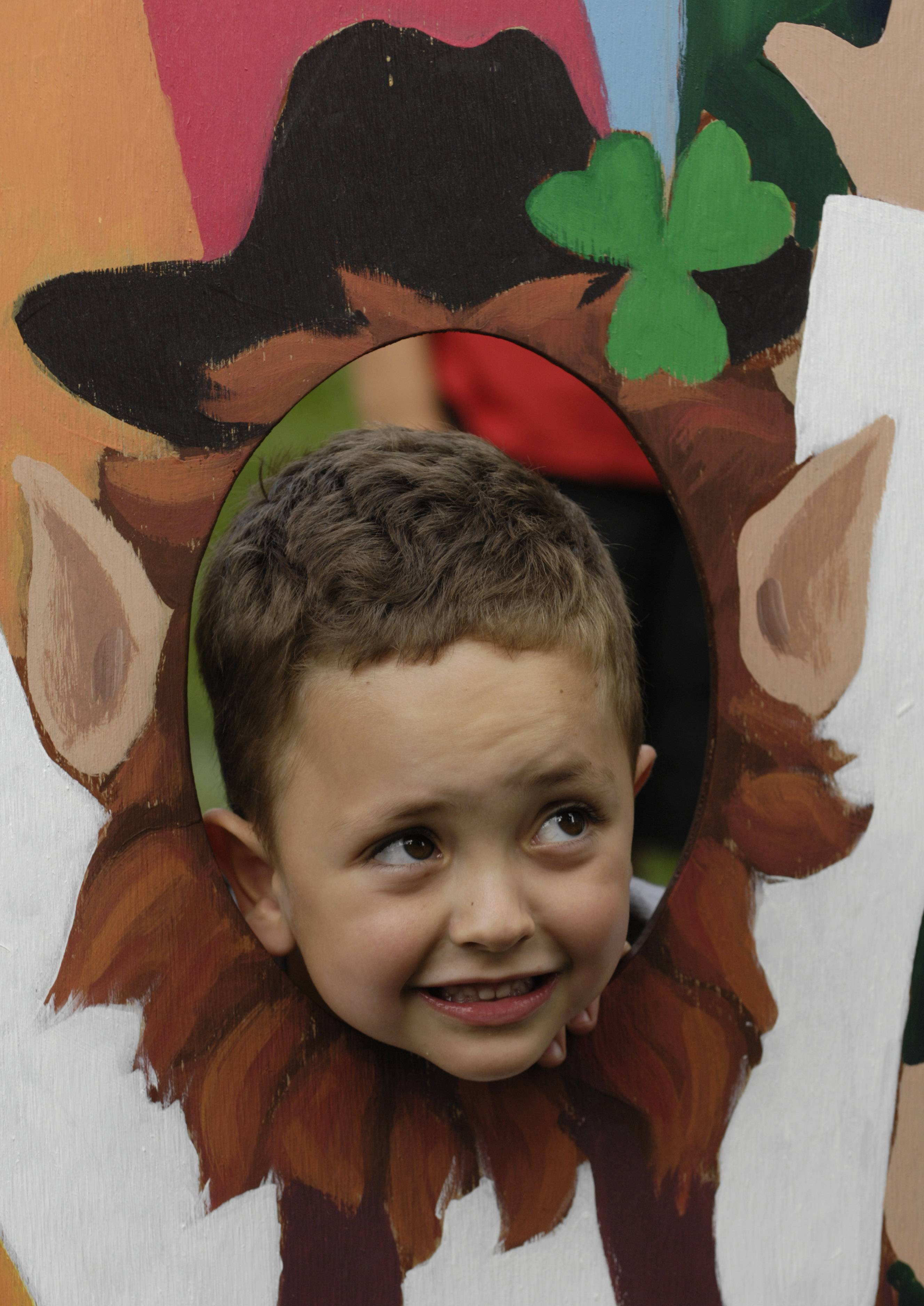 Nathan Oberg, 4, of Rockford sticks his head through a plywood leprechaun cutout during Friday's Irish Fest in Arlington Heights while visiting the event with his grandmother, a resident of the village.