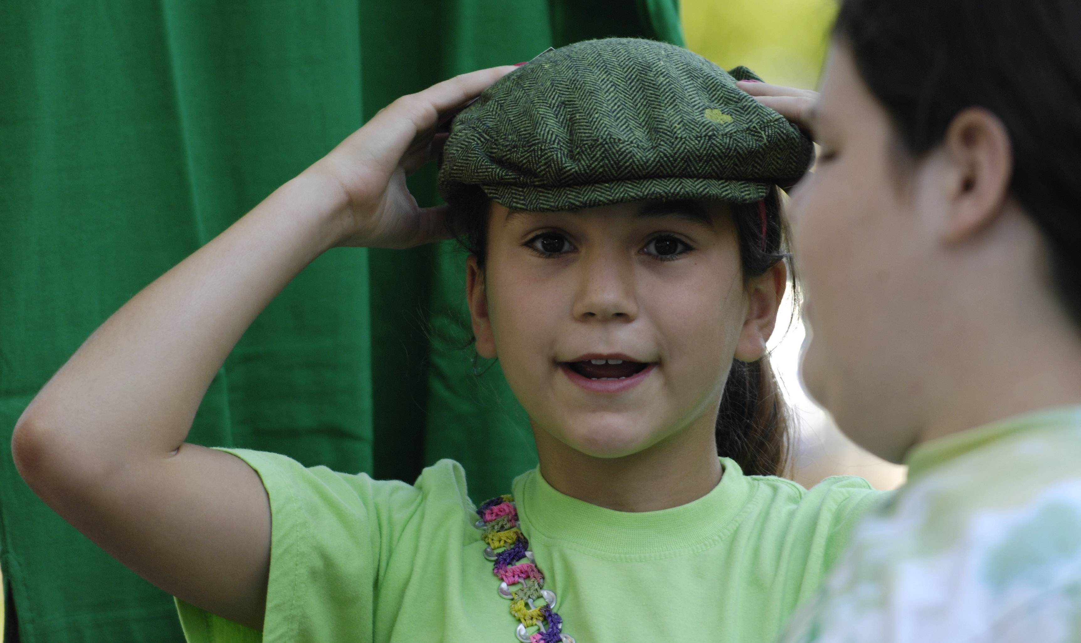 Annie Piet, left, tries on a hat while attending Irish Fest with friend Nary Naughton on Friday in Arlington Heights Friday. Both girls are 11 years old and live in Arlington Heights.