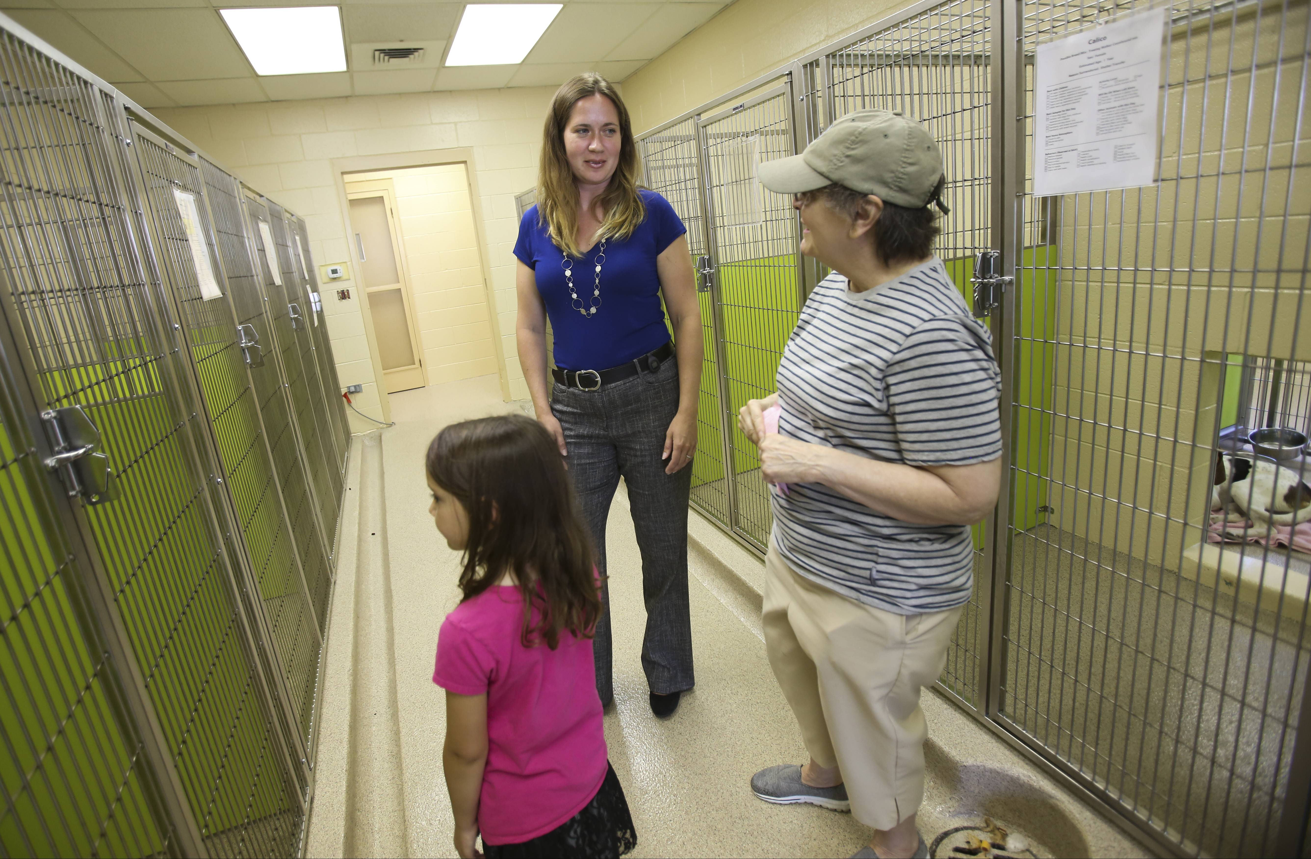 Anna Payton, who took over as executive director of the Naperville Area Humane Society in May, chats with Daniella Walczak and her 6-year-old granddaughter Karissa, who were looking at dogs to adopt from the shelter.