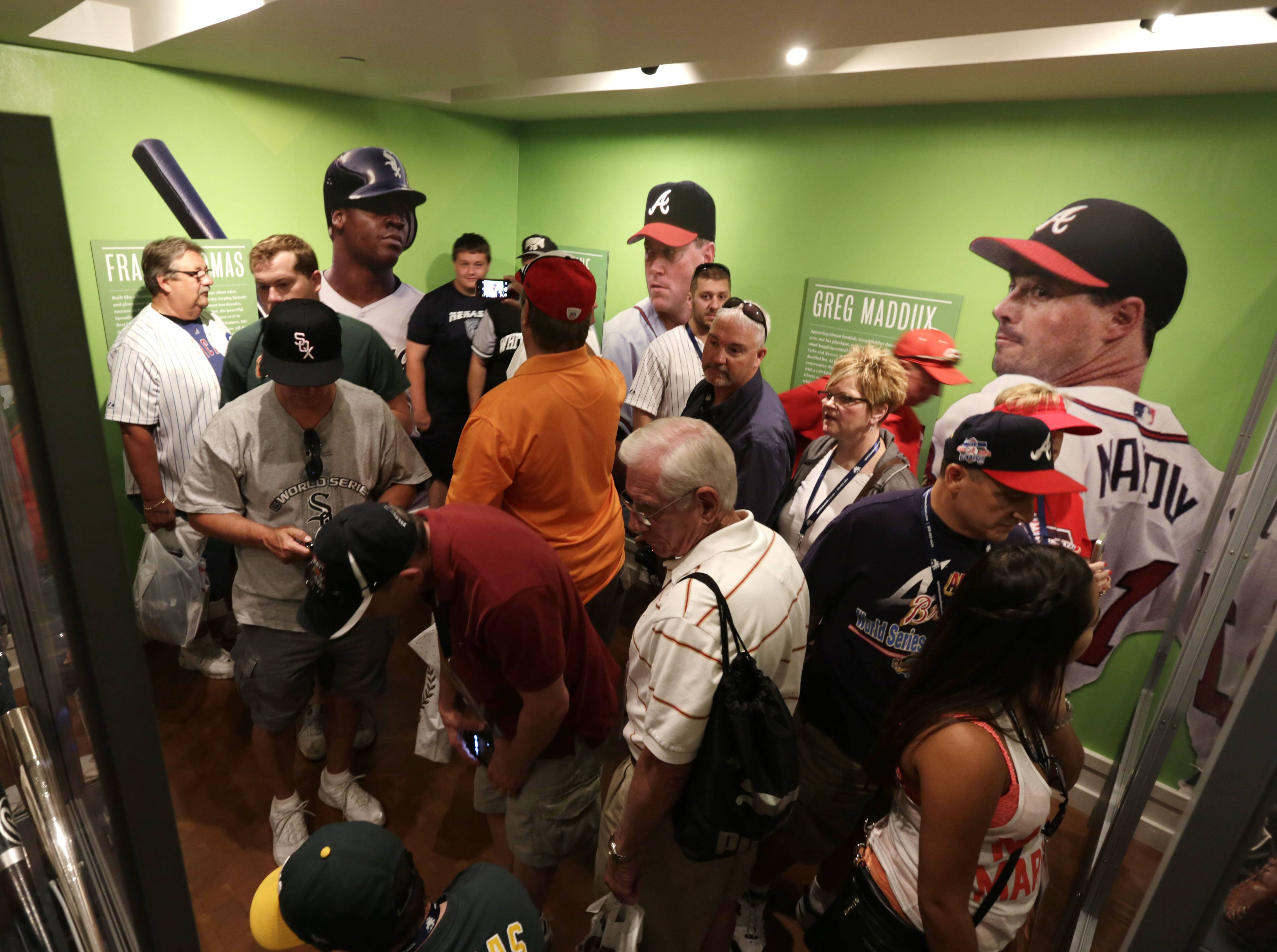 Fans visit displays of Frank Thomas, Tom Glavine and Greg Maddux at the Baseball Hall of Fame on Saturday, July 26, 2014, in Cooperstown, N.Y. The former Major League Baseball players will be inducted to the hall on Sunday.