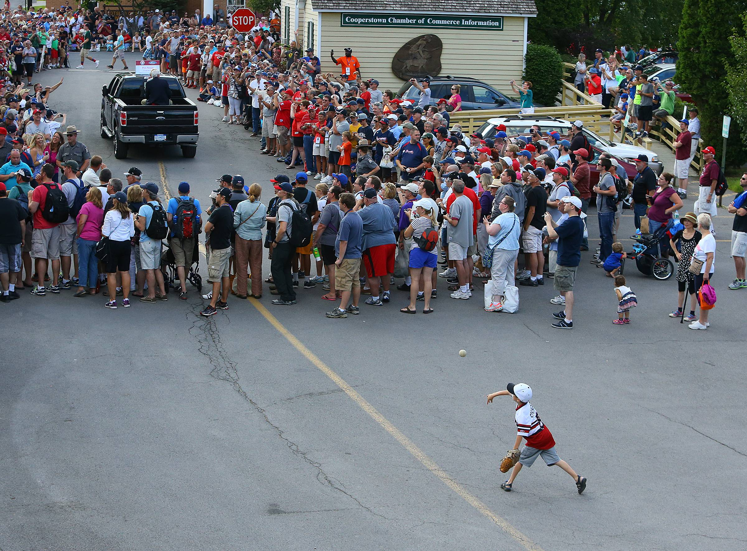 J.T. Stringer, 7, lower right, of Chicago, plays baseball in the street while the Hall of Fame Legends Parade passes by on the way to Main Street on Saturday, July 26, 2014, in Cooperstown, N.Y.