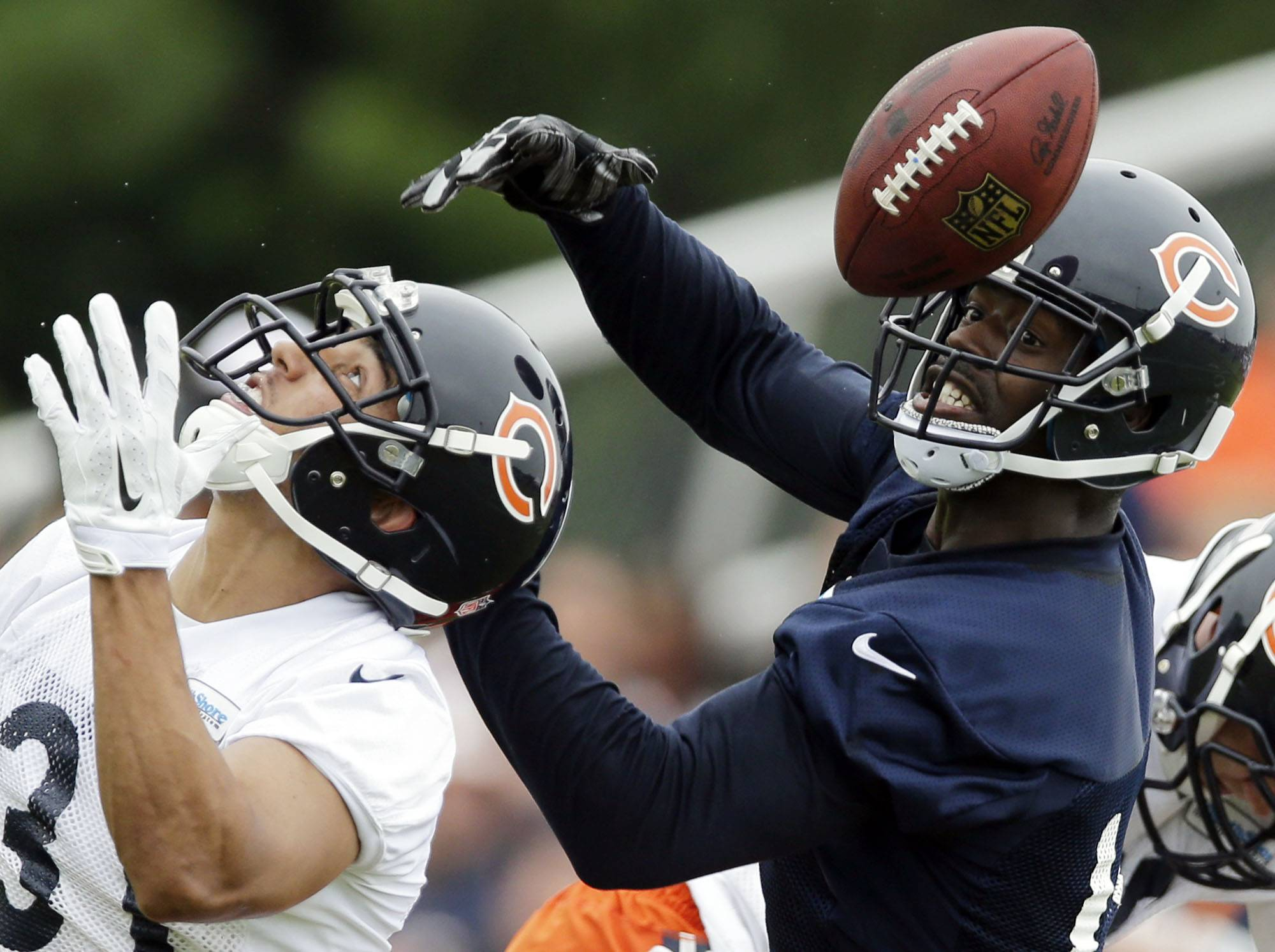Bears wide receiver Josh Morgan, right, and cornerback Isaiah Frey try to catch a ball Saturday during training camp in Bourbonnais, Ill.