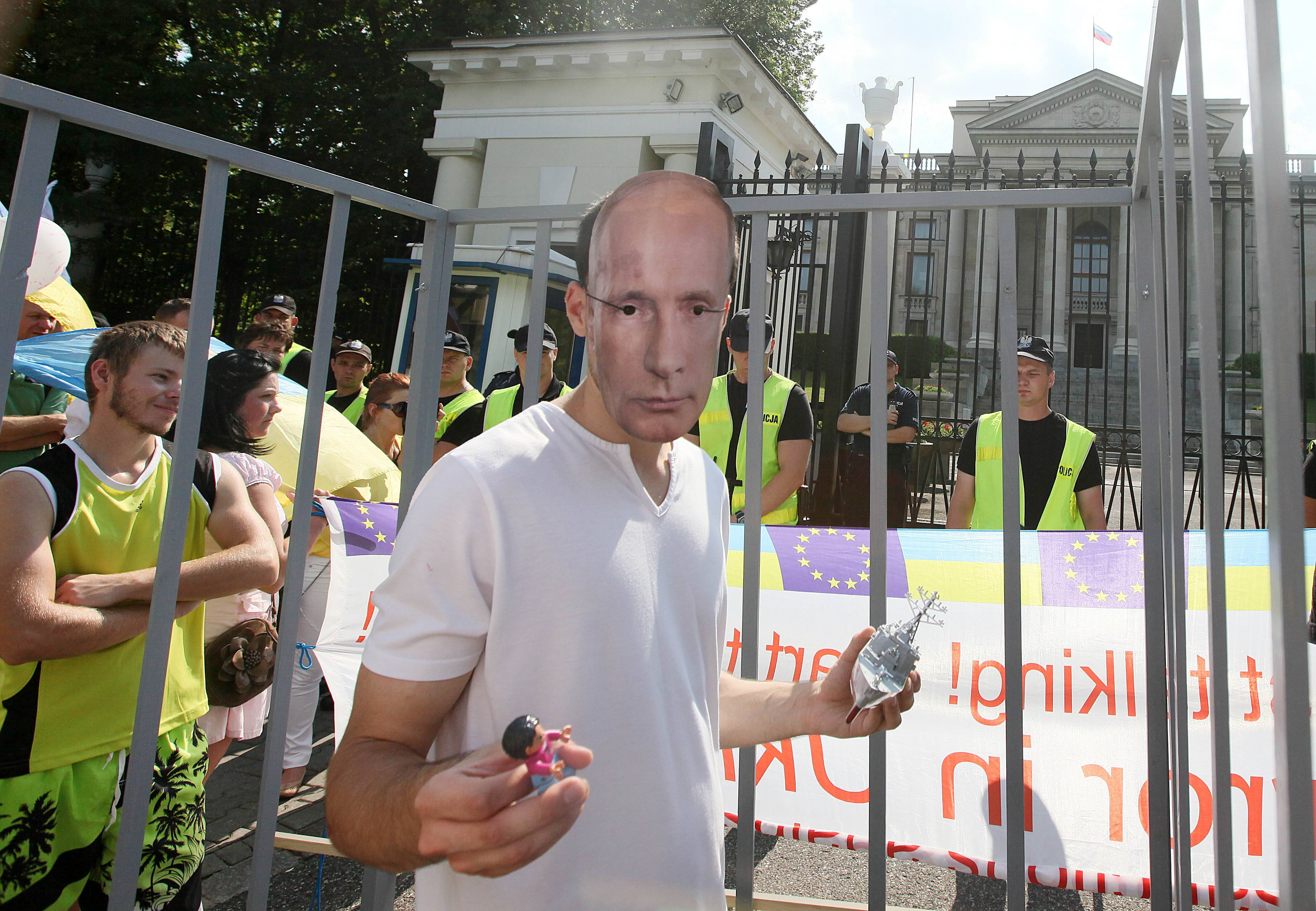A protester wears a mask depicting Russian President Vladimir Putin , during a a protest against Russia's behavior in the Ukraine conflict, in front of the Russian Embassy in Warsaw, Poland, on Sunday July 27, 2014. .(AP Photo/Czarek Sokolowski)