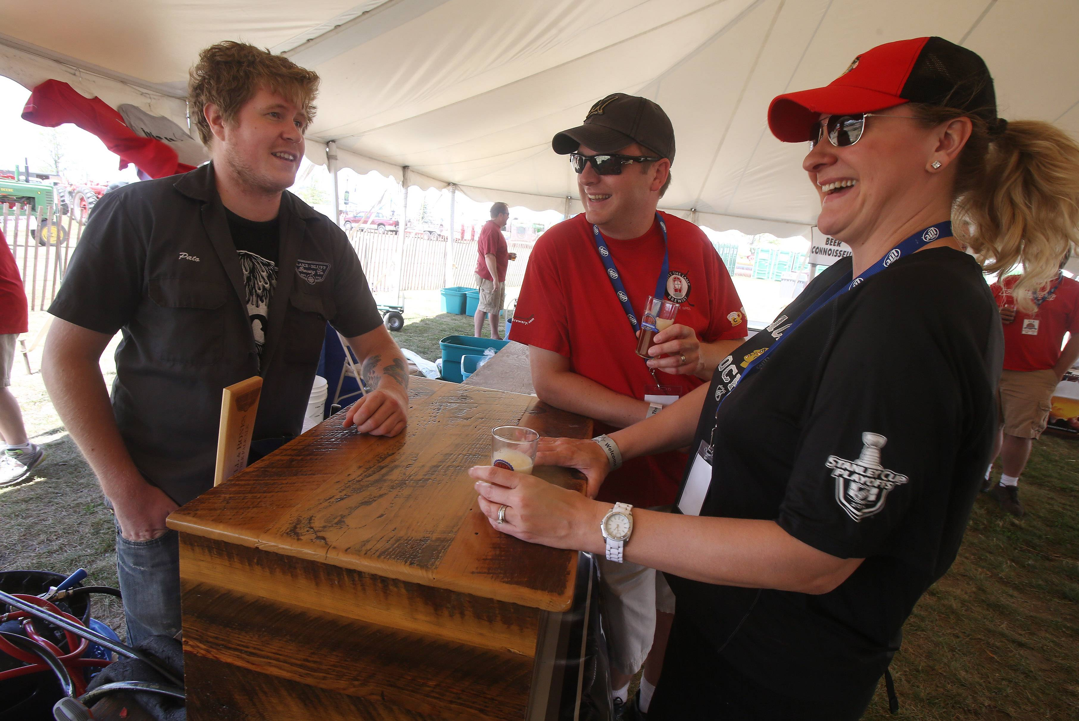 Pato Thornycroft of Lake Bluff Brewery Co., talks with Victor and Pam Dobrogowski of Mundelein during the Craft Beer Festival at the Lake County Fair at the fairgrounds in Grayslake. Sunday's other fair events featured the demolition derby, wool spinning demonstration, talent shows and more.