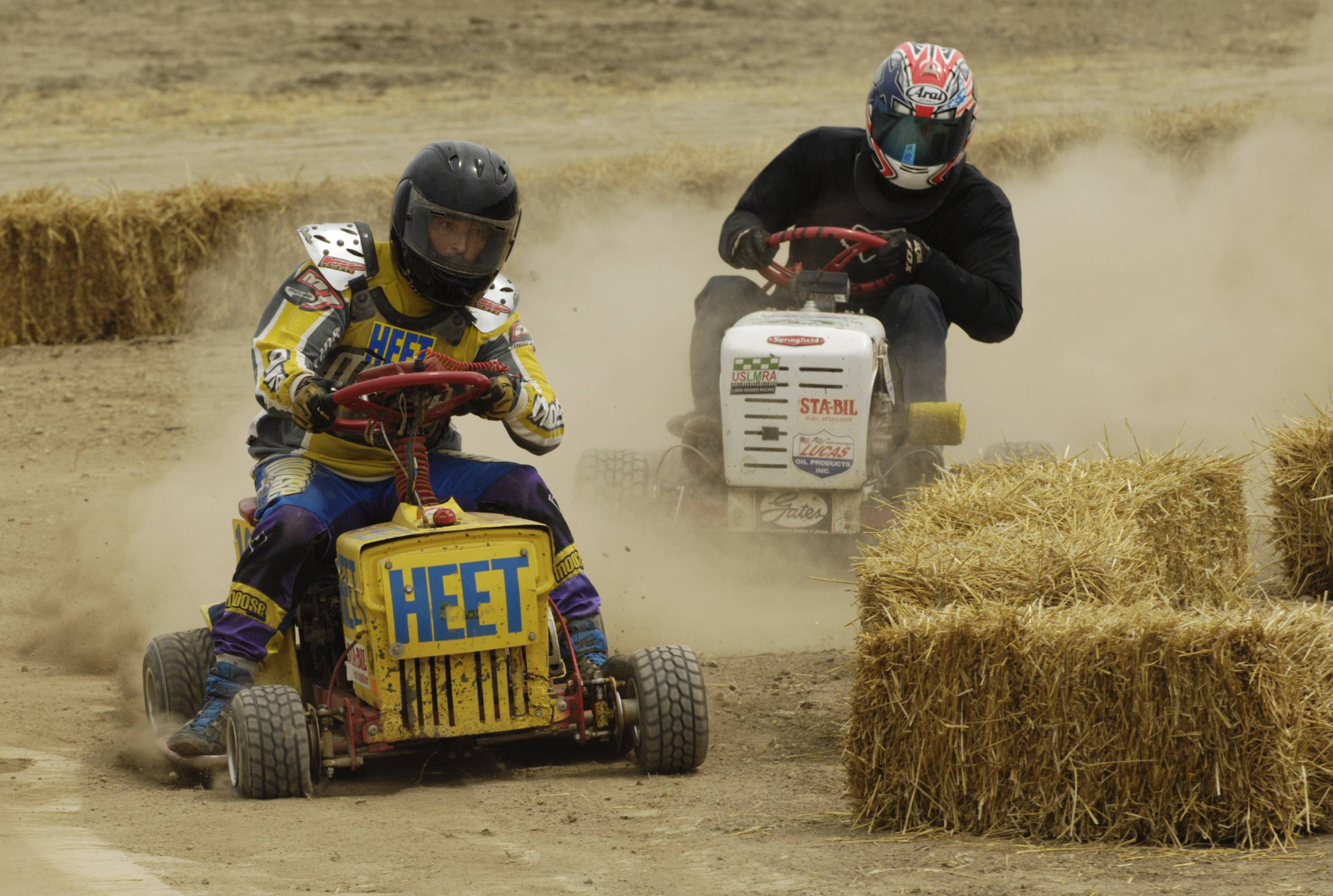"Competitors in the ""Mow Down Showdown"" lawn mower races speed around a turn at Lake County Fair in Grayslake Saturday."