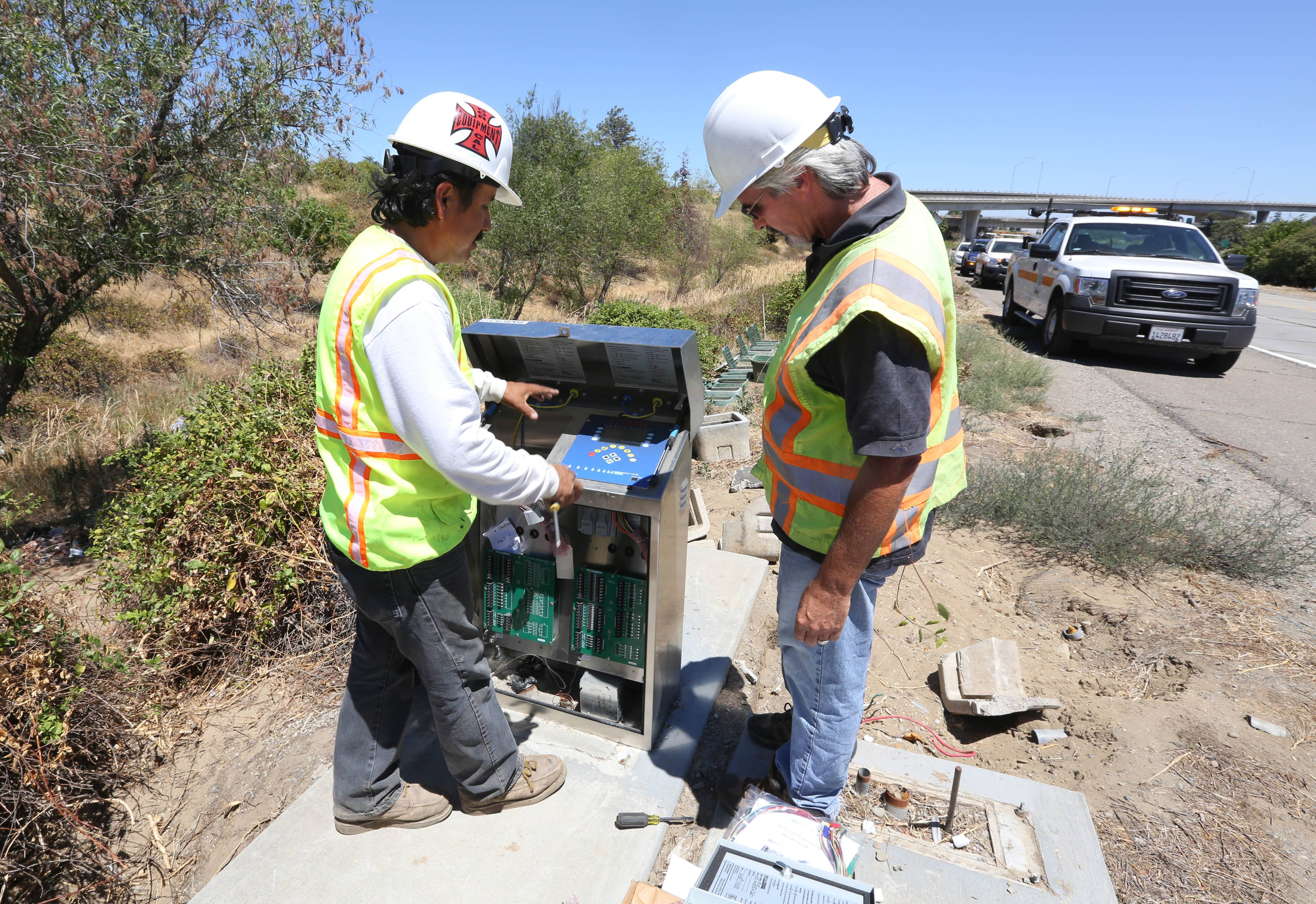 Russ Lake, a field inspector for the California Department of Transportation, right, looks over a remote water management controller just installed by Lionel Flores along Highway 4 in Stockton, Calif. From these control units, Caltrans can monitor water flow from a central office looking for excessive water usage caused by leaks or breaks in the system.