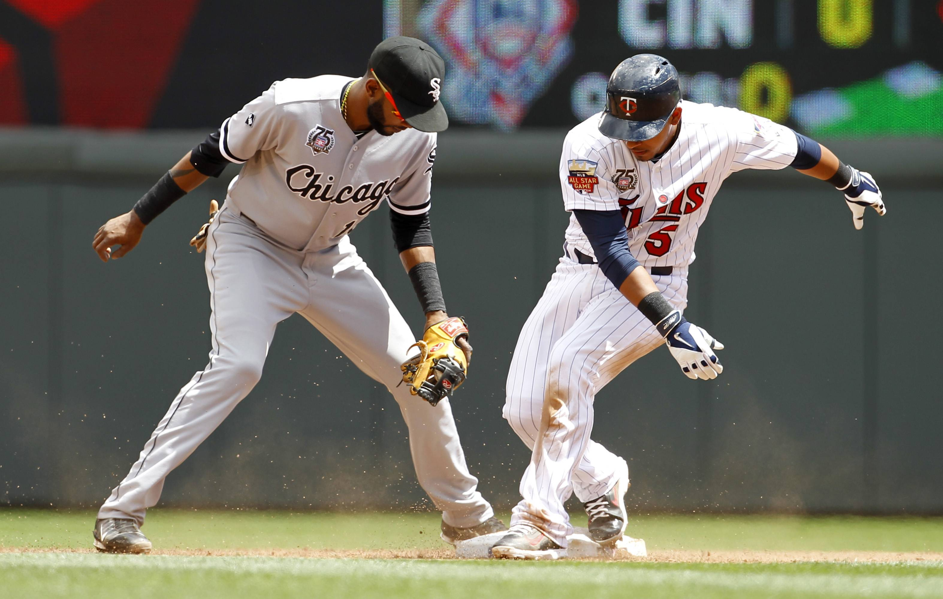 Minnesota Twins' Eduardo Escobar, right, makes it safely to second base on a double to right as Chicago White Sox shortstop Alexei Ramirez gets the late throw during the third inning of a baseball game in Minneapolis, Sunday, July 27, 2014.