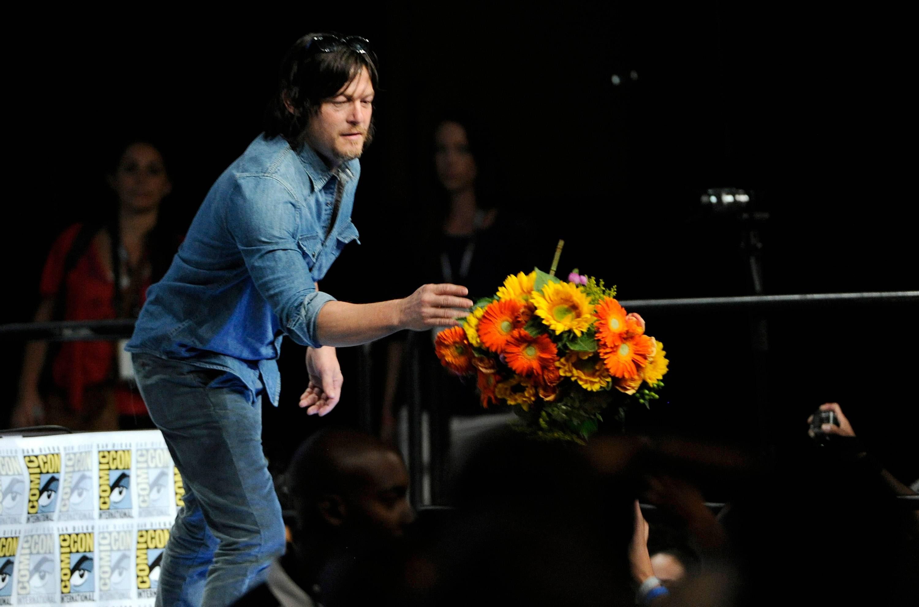 "Norman Reedus throws flowers to the audience at ""The Walking Dead"" panel on Day 2 of Comic-Con International on Friday in San Diego."