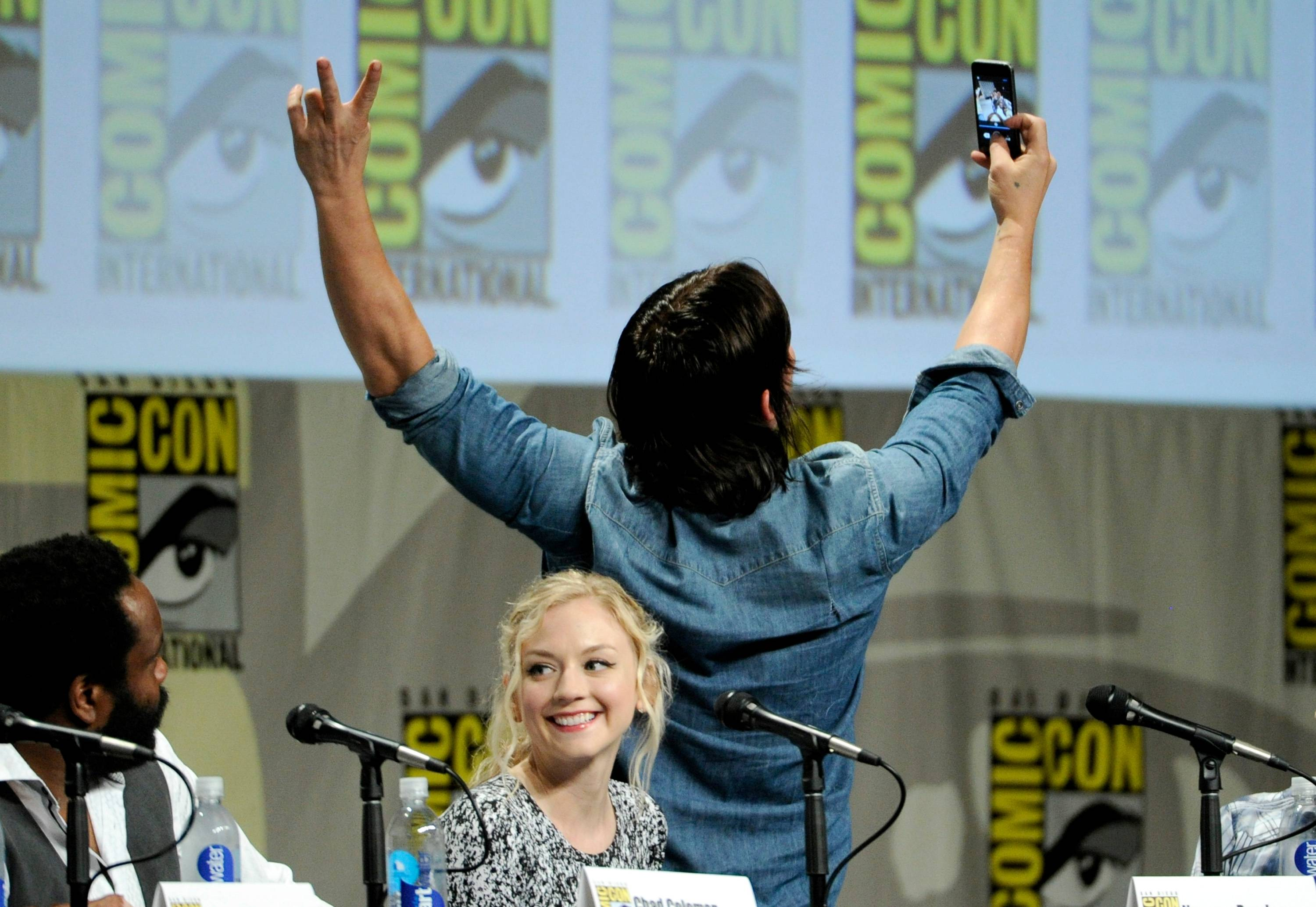 "Norman Reedus, right, takes a selfie at ""The Walking Dead"" panel on Day 2 of Comic-Con International on Friday. Looking on from left are Chad Coleman and Emily Kinney."