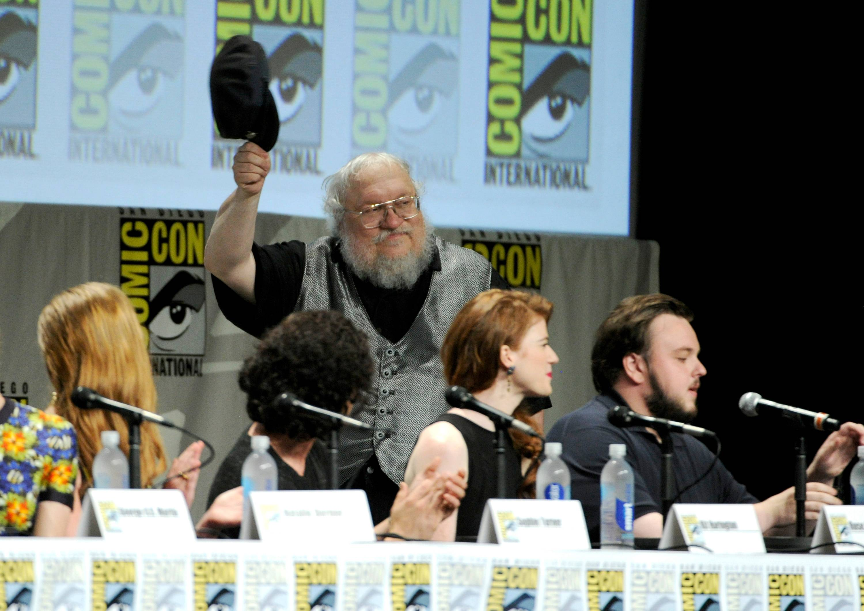 "George R.R. Martin attends the ""Game of Thrones"" panel on Day 2 of Comic-Con International on Friday. Looking on from left are Sophie Turner, Kit Harington, Rose Leslie and John Bradley."