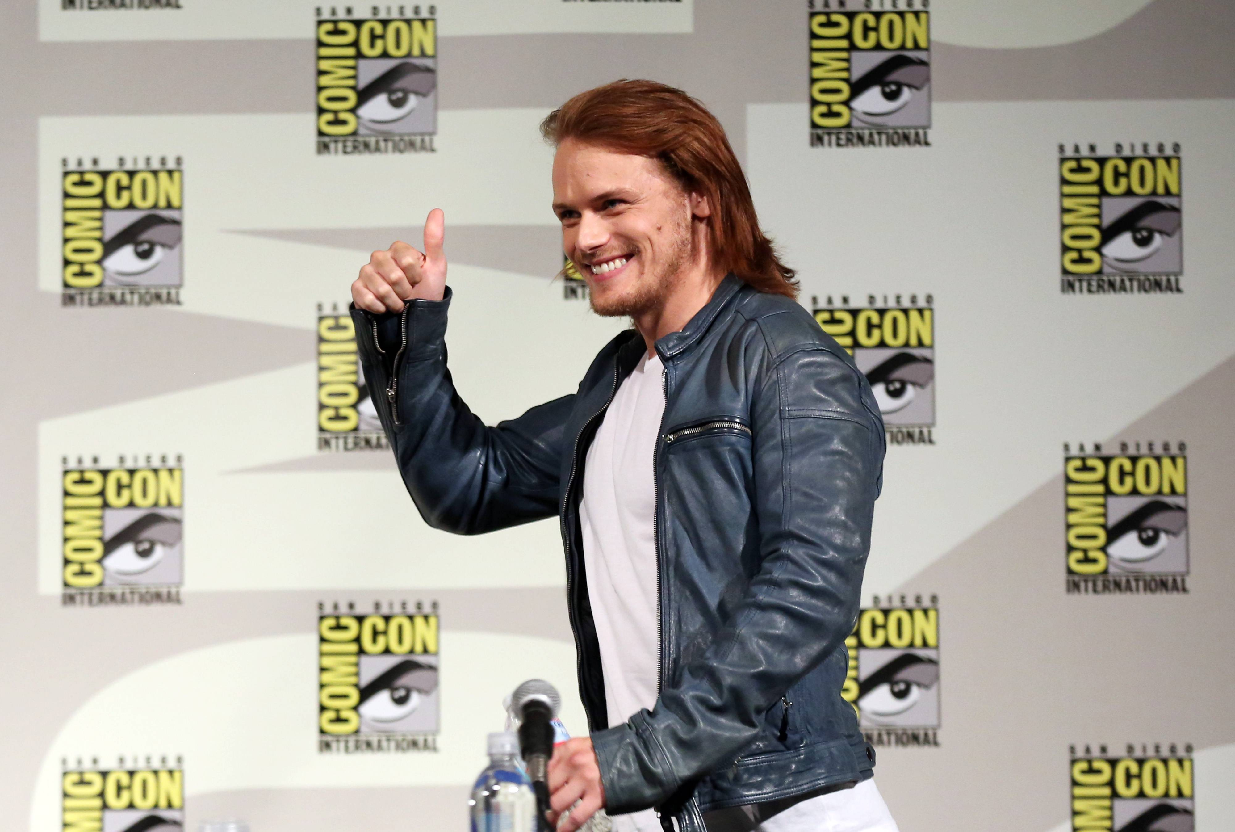 "Actor Sam Heughan walks onstage at the STARZ ""Outlander"" panel during San Diego Comic-Con on Friday."