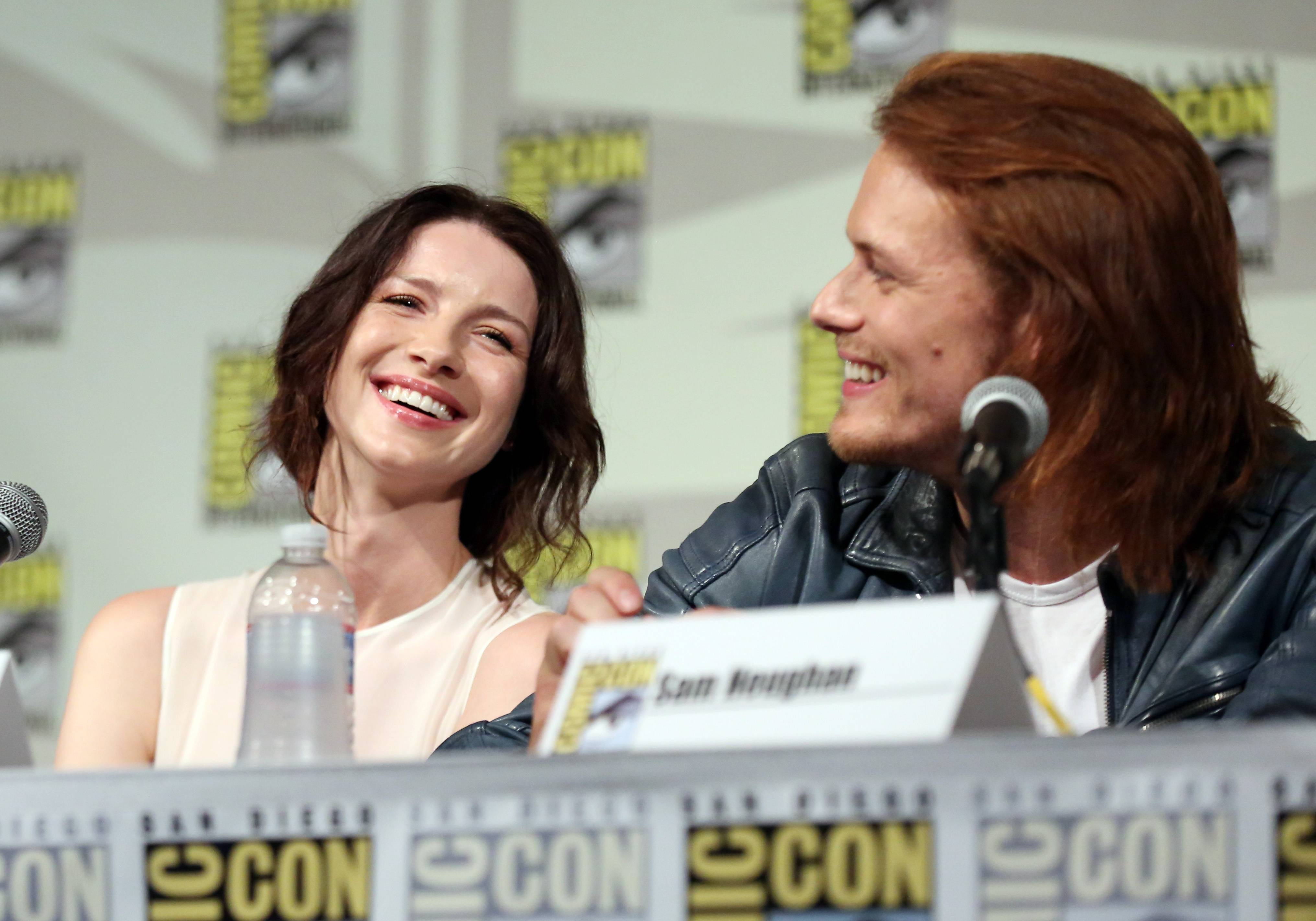 "Caitriona Balfe, left, and Sam Heughan are seen onstage at the STARZ ""Outlander"" panel during San Diego Comic-Con on Friday."
