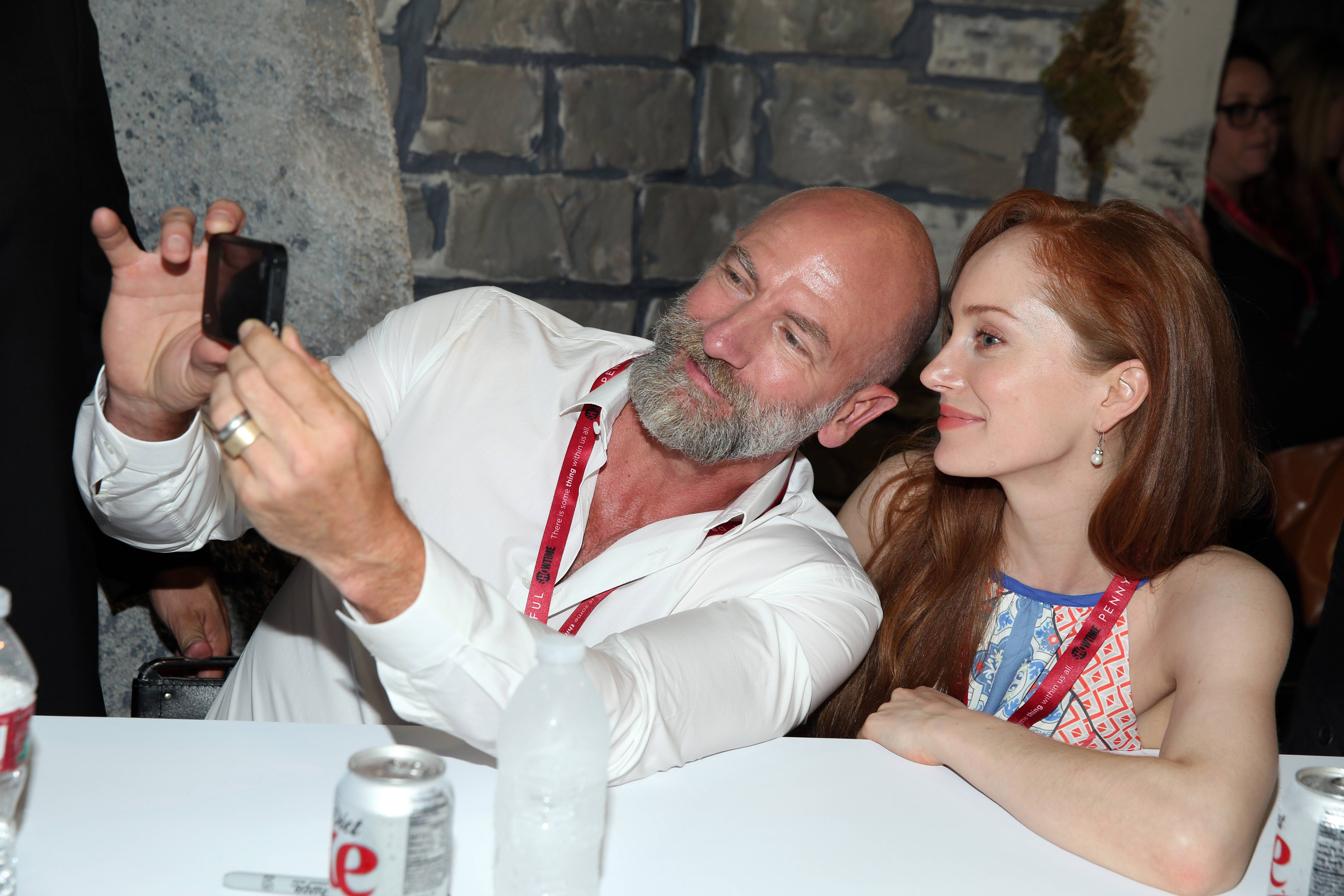 "Graham McTavish, left, and Lotte Verbeek take a picture during an autograph signing for the STARZ original series ""Outlander"" at San Diego Comic-Con on Friday."