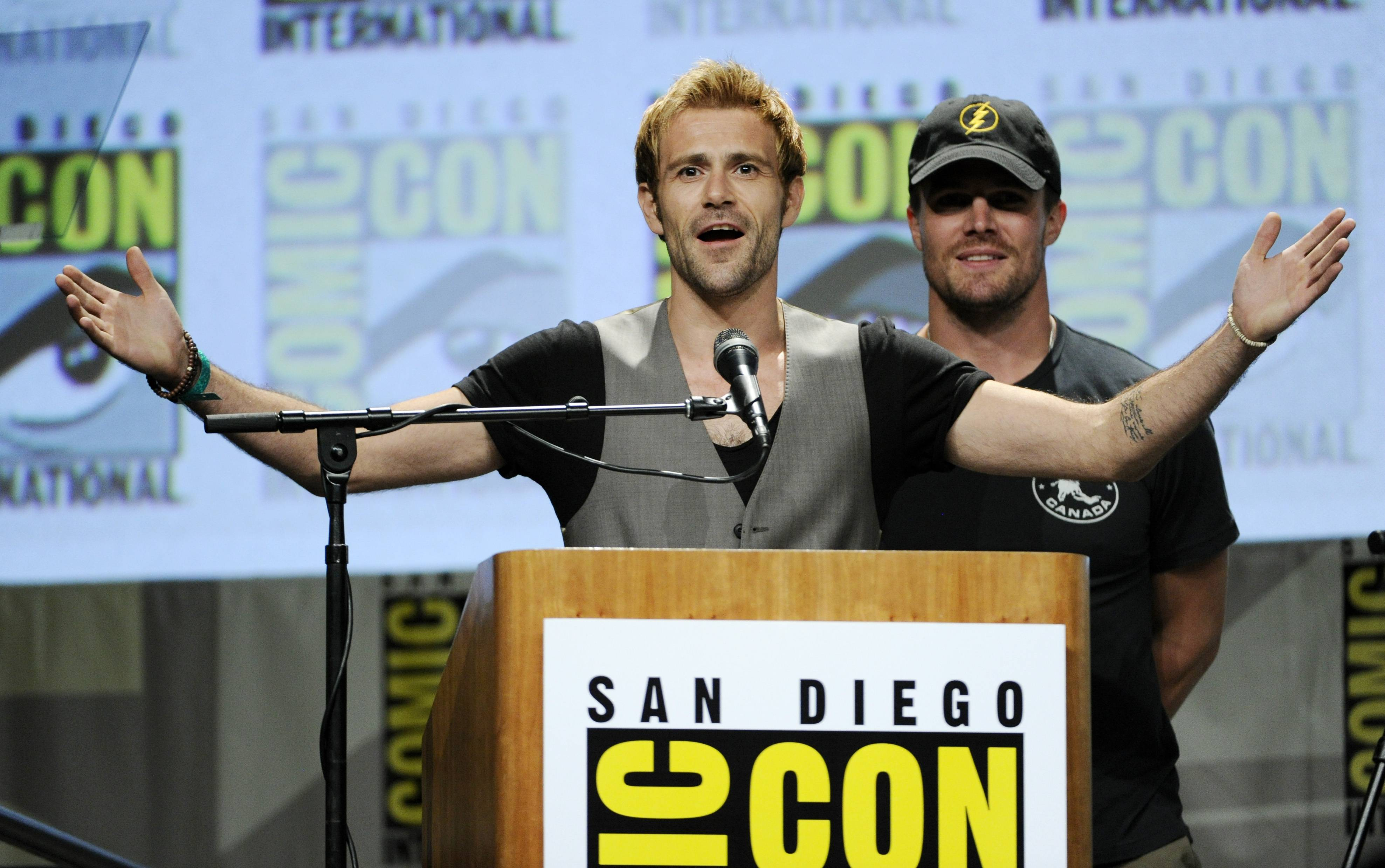 "Matt Ryan, left, a cast member in the television series ""Constantine,"" introduces a clip from the series for the audience as host Stephen Amell looks on at Comic-Con International on Saturday in San Diego."