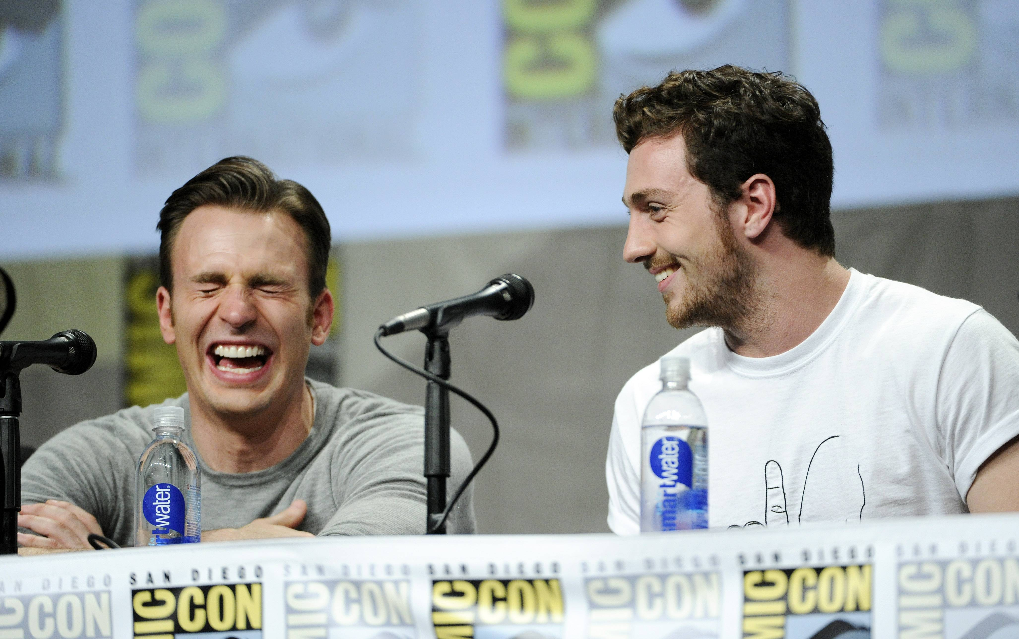 Actors Chris Evans, left, and Aaron Taylor-Johnson laugh during the Marvel panel at Comic-Con International on Saturday.