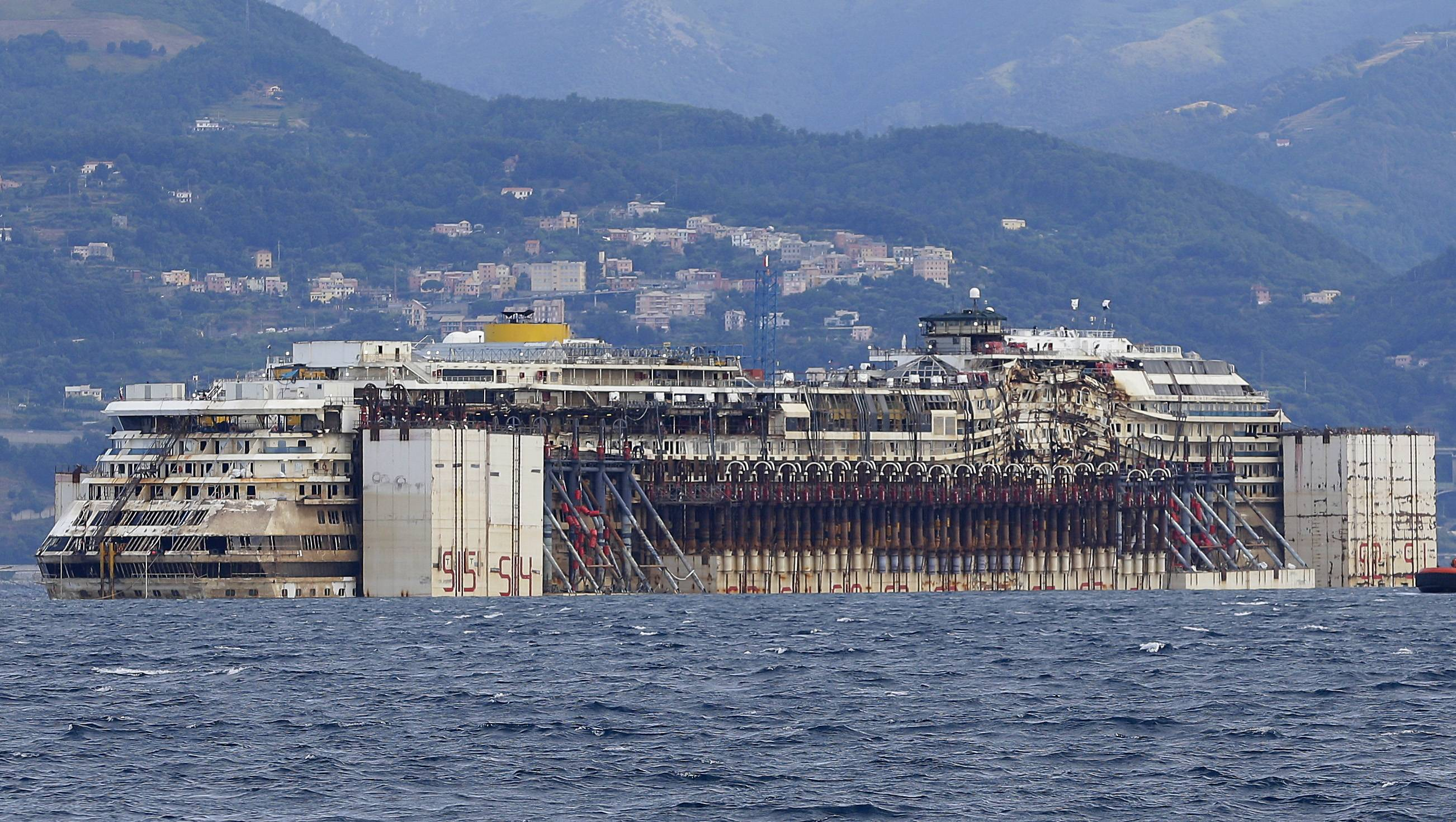The wreck of the Costa Concordia cruise ship is towed by tugboats towards Genoa's harbor, Italy, Sunday. The luxury liner struck a reef when its captain sailed too close to Giglio Island off Tuscany's coast Jan. 13, 2012, and capsized, killing 32 people.