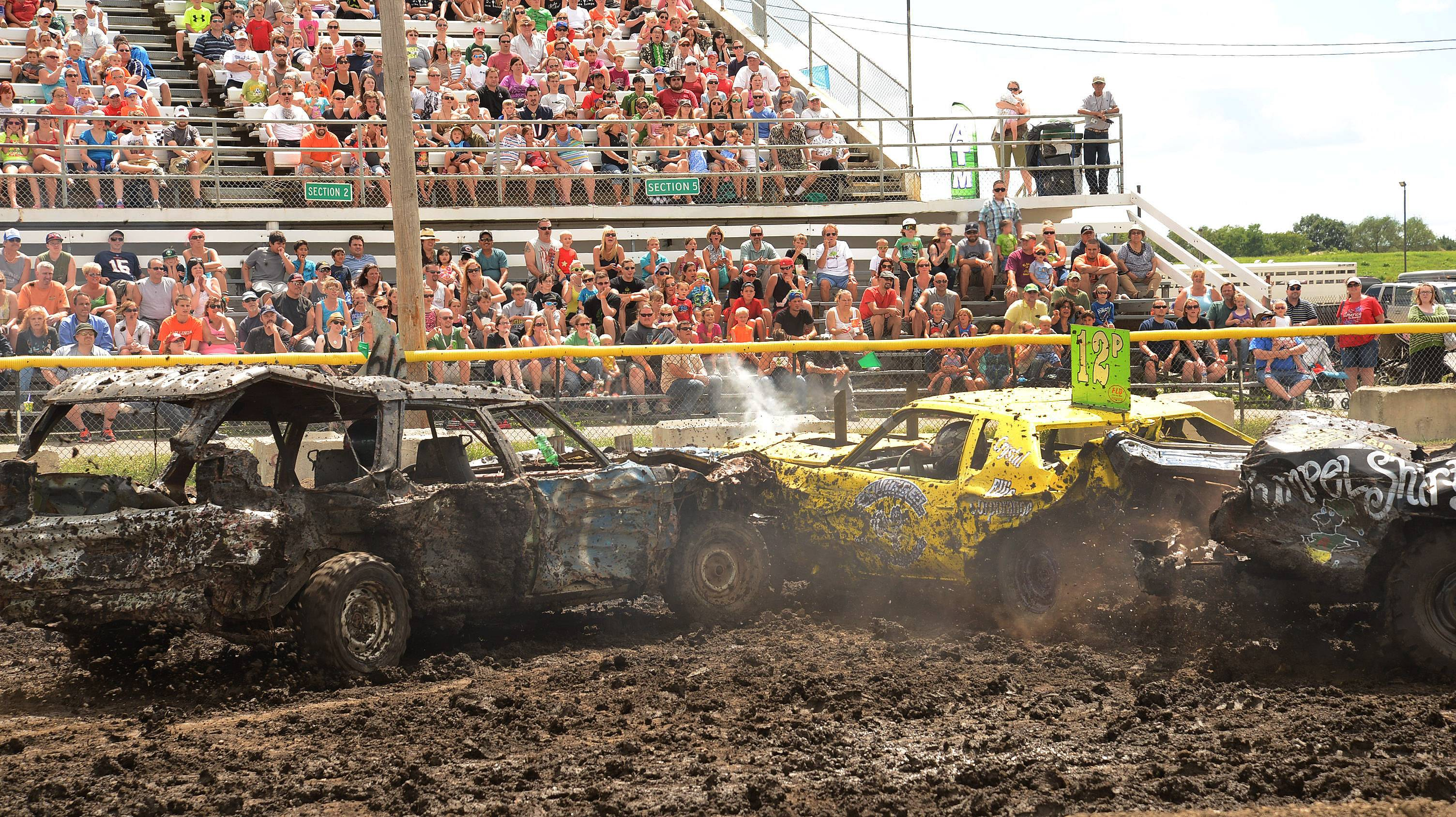 From left, Ray Green of Marengo, Patrick Wyller of Wheaton and Jay Oppenheim of Wheaton get tangled up Sunday during the demolition derby on the last day of the DuPage County Fair.