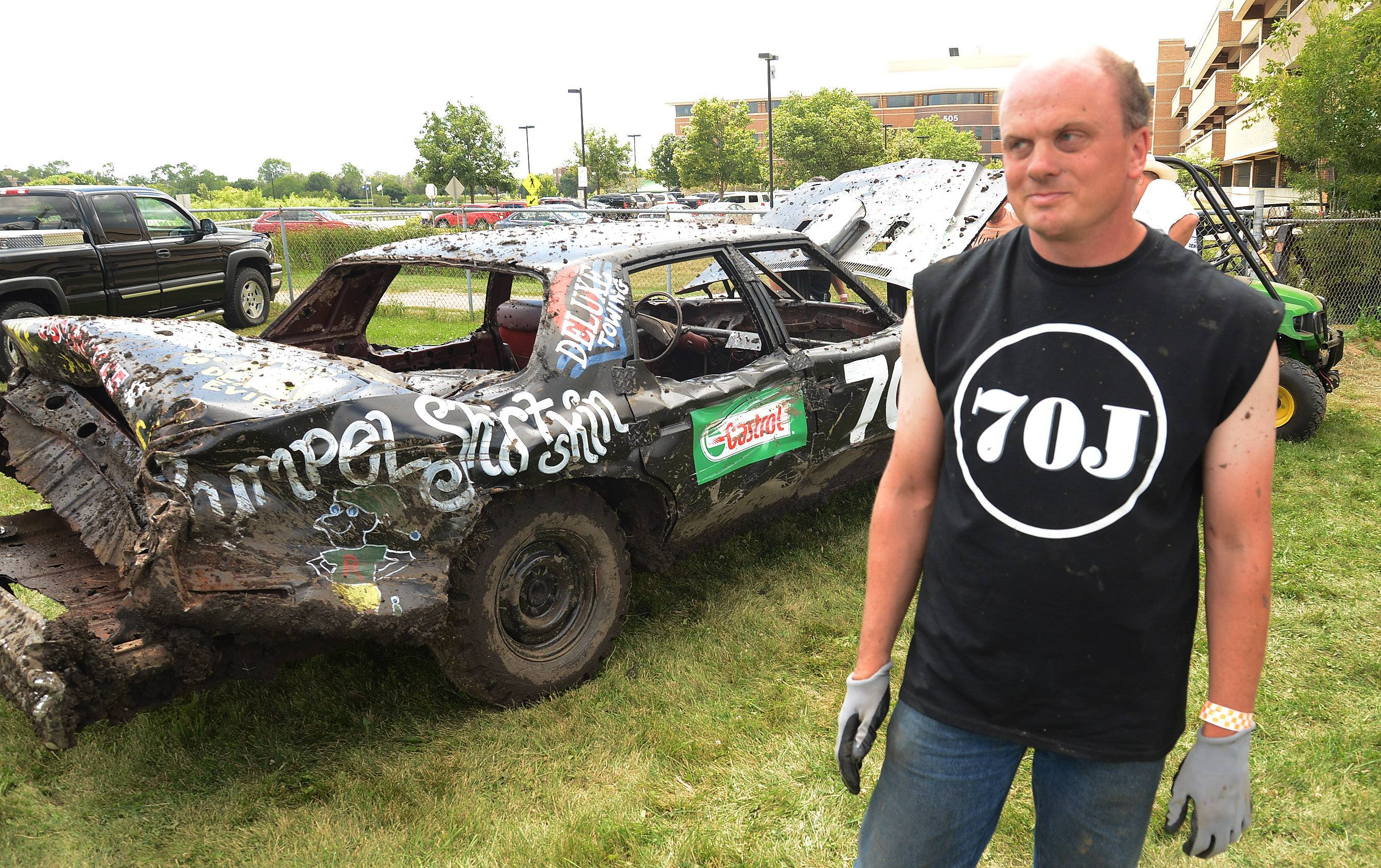 Jay Oppenheim of Wheaton stands alongside his car after qualifying for the final of the demolition derby at the DuPage County Fair. The derby was among the highlights of the fair's final day.