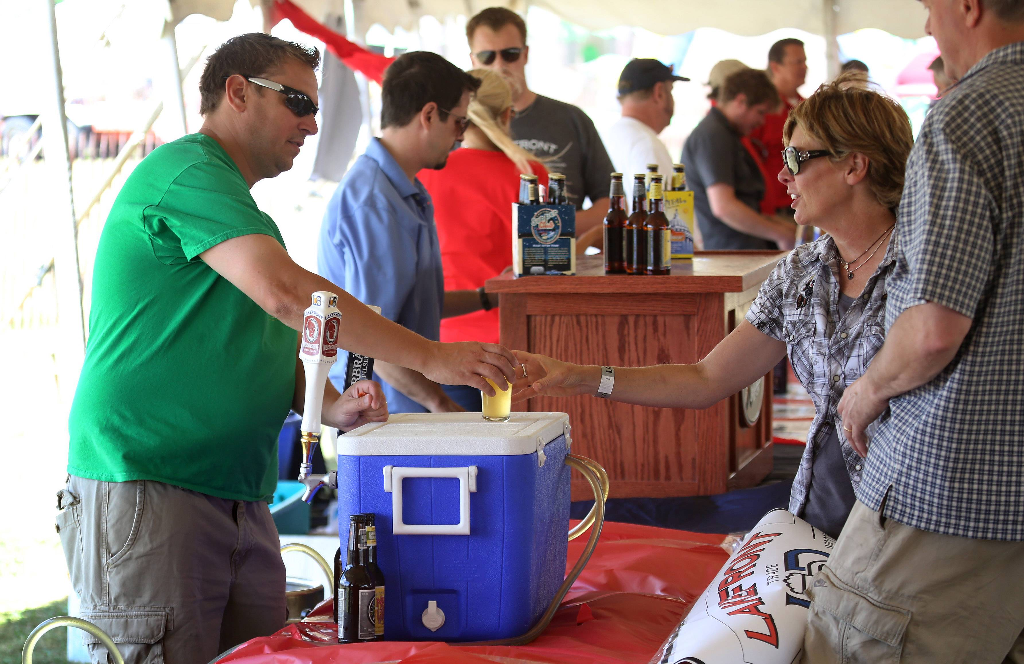 Brian Cooper of Baderbrau Brewery serves beer to Missy Foss of Third Lake during Sunday's inaugural Craft Beer Festival at the Lake County Fair in Grayslake.