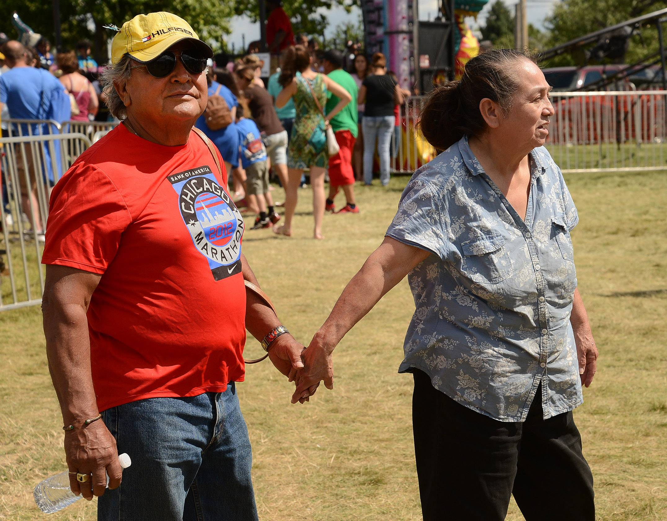 Felipe De La Rosa of Streamwood and his wife, Anita, watch their great-granddaughter on one of the rides as they stroll the midway Sunday during the final day of the Streamwood Summer Celebration.