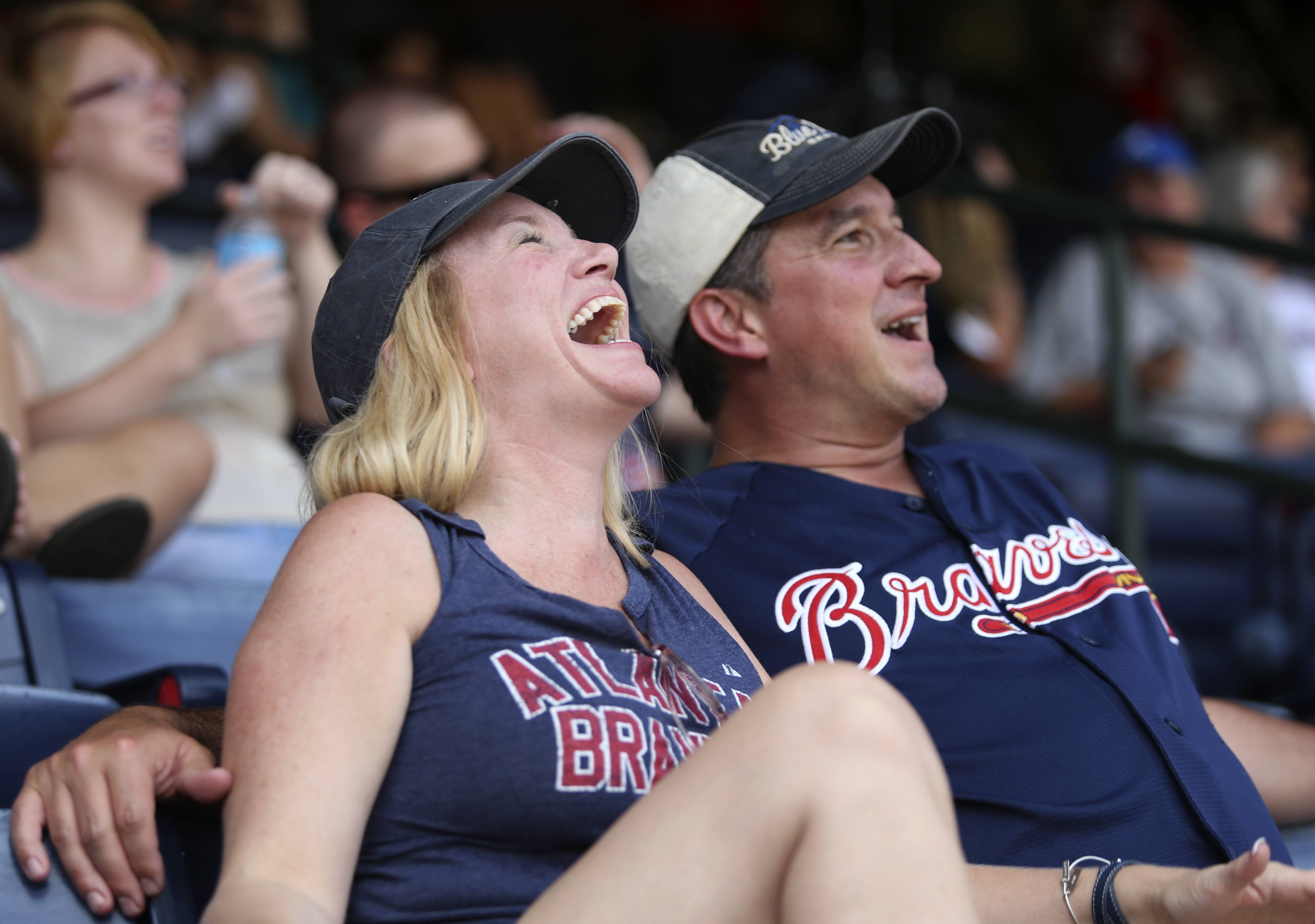 Merry, left, and her husband Mike Quarles, of Woodstock, Ga., react to a comment by former Atlanta Braves manager Bobby Cox as they watched the broadcast of the Baseball Hall of Fame induction ceremony, before the Braves' game against the San Diego Padres at Turner Field on Sunday afternoon, July 27, 2014, in Atlanta. Three former Braves--manager Bobby Cox and pitchers Greg Maddux and Tom Glavine--were inducted into the hall on Sunday.