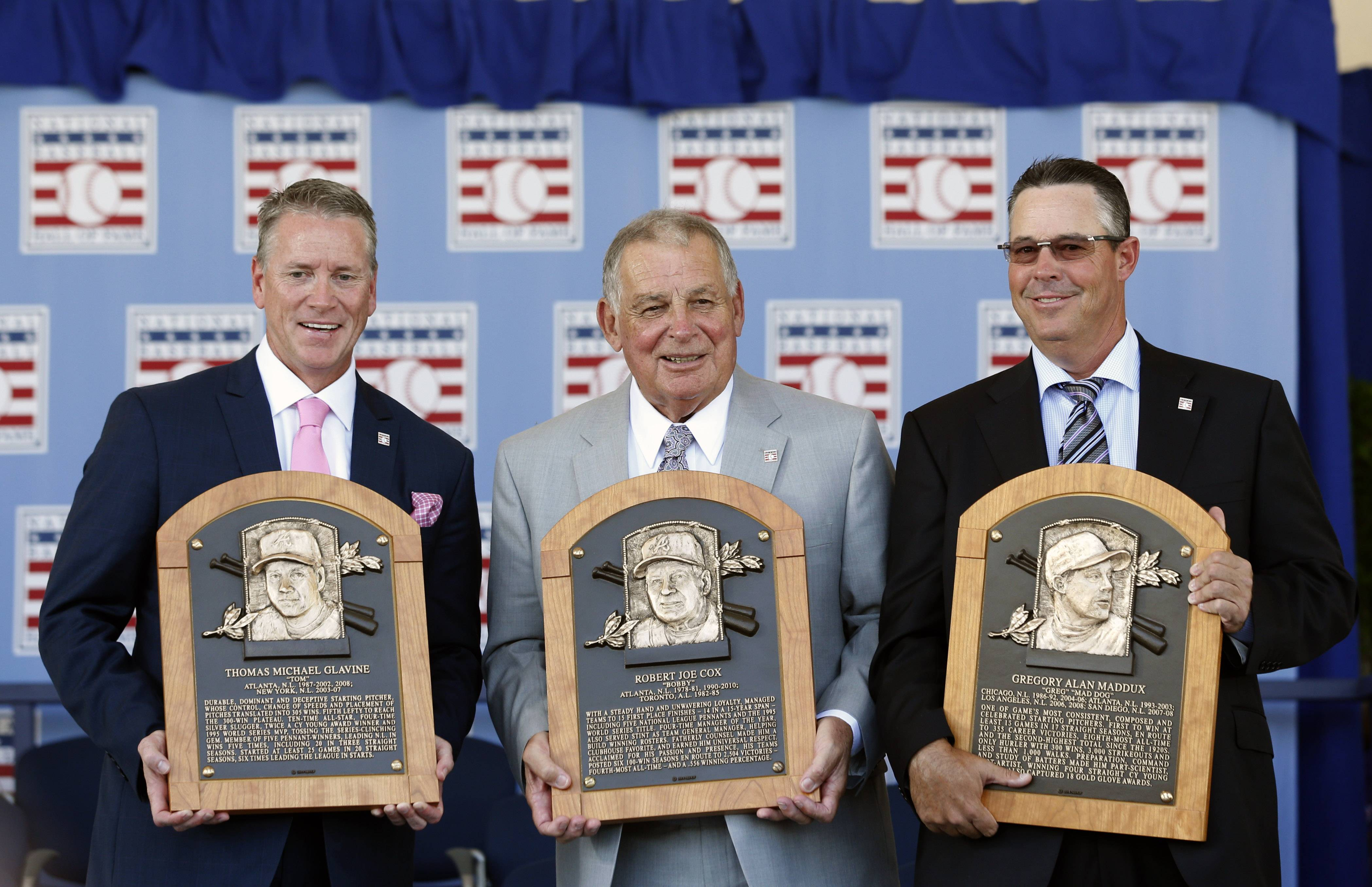 National Baseball Hall of Fame inductees Tom Glavine, left,  Bobby Cox and Greg Maddux, right,  hold their plaques after an induction ceremony at the Clark Sports Center on Sunday, July 27, 2014, in Cooperstown, N.Y.