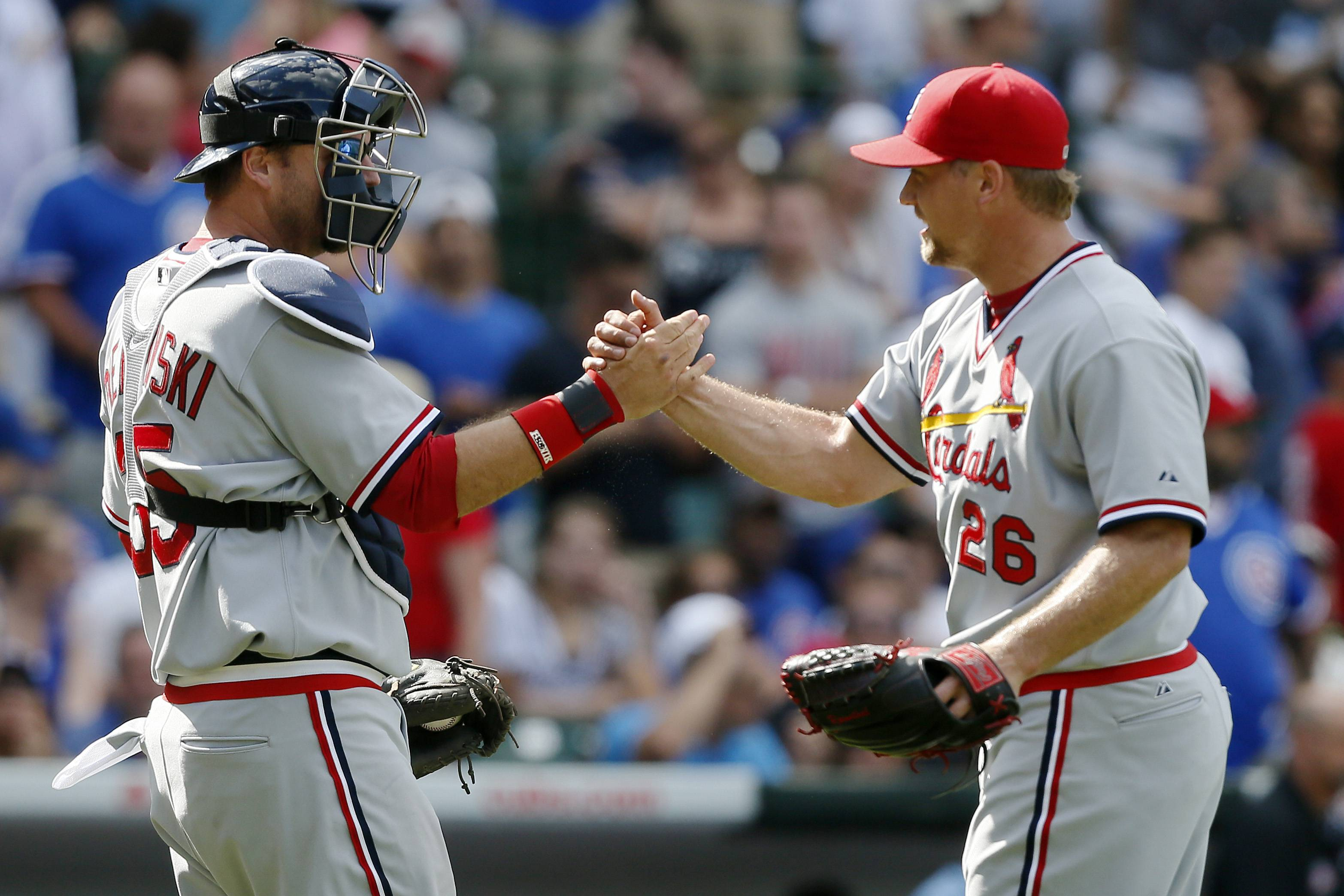 St. Louis Cardinals catcher A.J. Pierzynski and relief pitcher Trevor Rosenthal celebrate after defeating the Chicago Cubs in a baseball game on Sunday, July 27, 2014, in Chicago. The St. Louis Cardinals won 1-0.