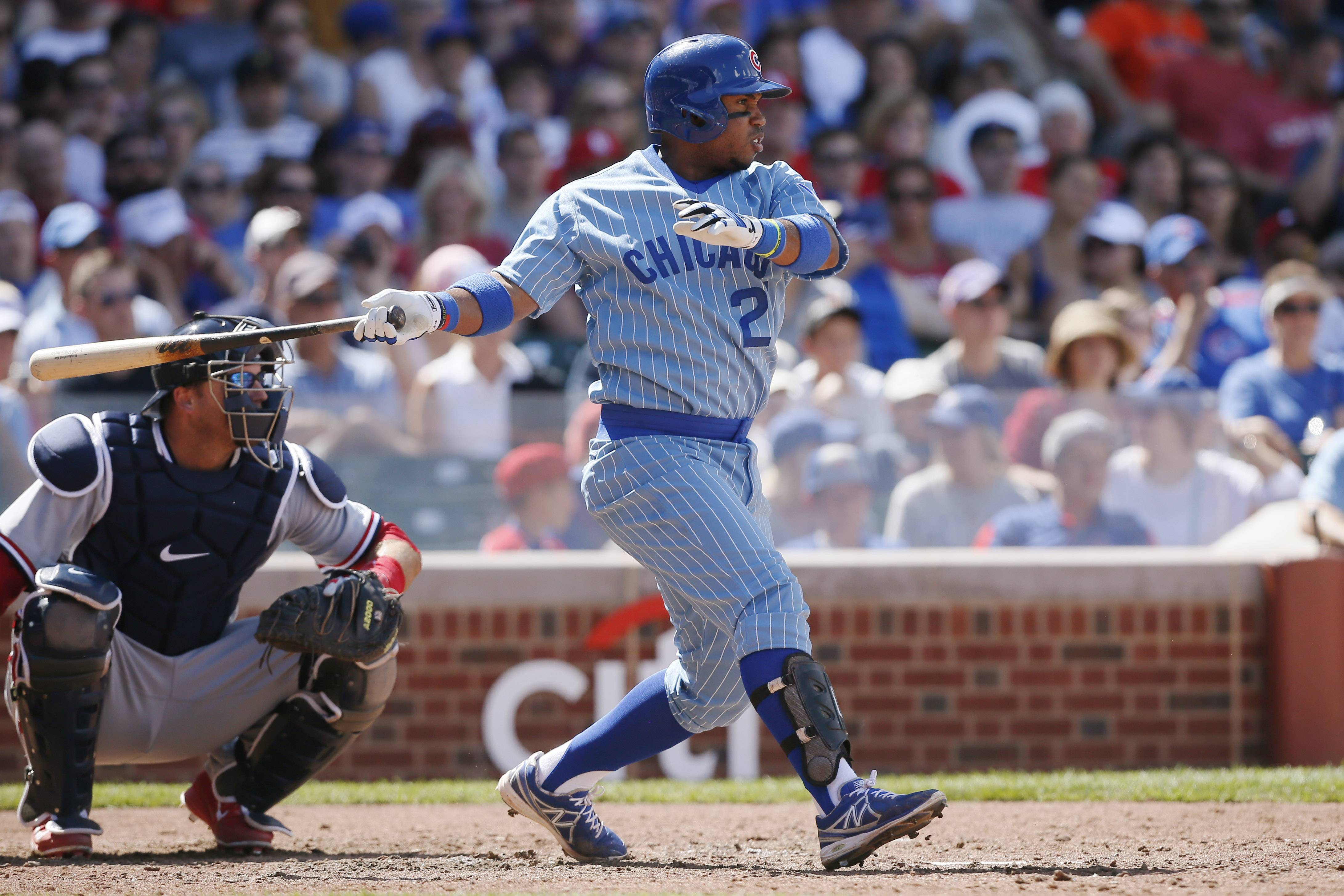 Chicago Cubs' Luis Valbuena, right, hits a single against the St. Louis Cardinals during the seventh inning of a baseball game on Sunday, July 27, 2014, in Chicago.