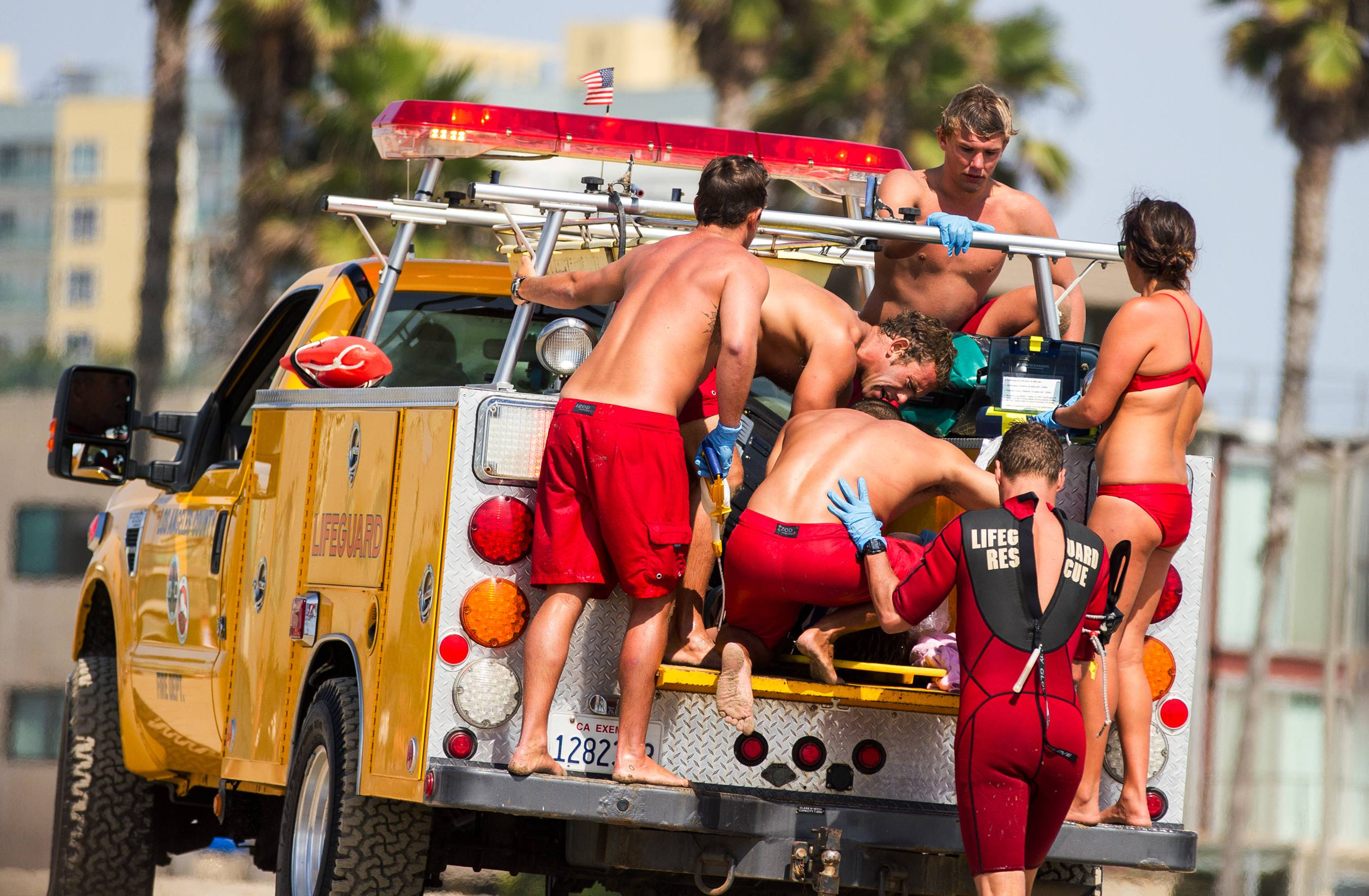 Lifeguards assist a person who was in the water and apparently struck by lightening Sunday in Los Angeles. Lightning struck 13 people, killing one, as rare summer thunderstorms swept through Southern California.