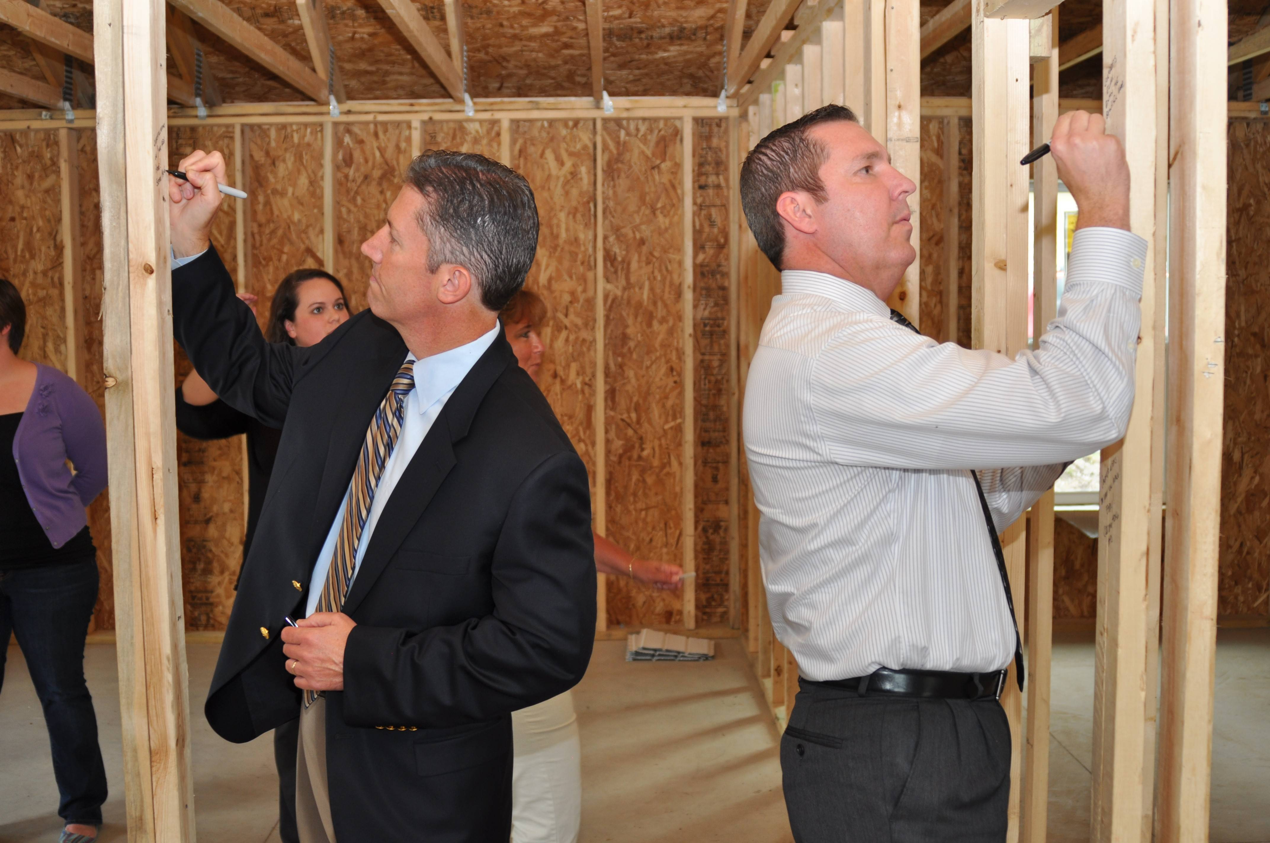 Geneva's Steve McCormick, left, and Dave McCormick of Batavia autographed timbers at a new Fox Valley Habitat for Humanity home in Aurora.