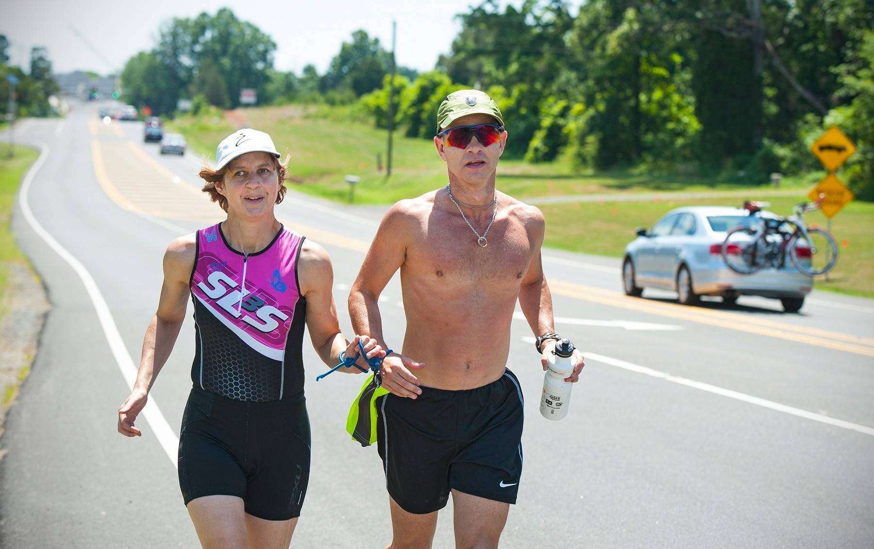 Tina Ament holds onto a bungie cord connected to her guide, Kevin Streeter, as they go for a run. Ament, who is blind, is training for the Ironman Triathlon in Hawaii.