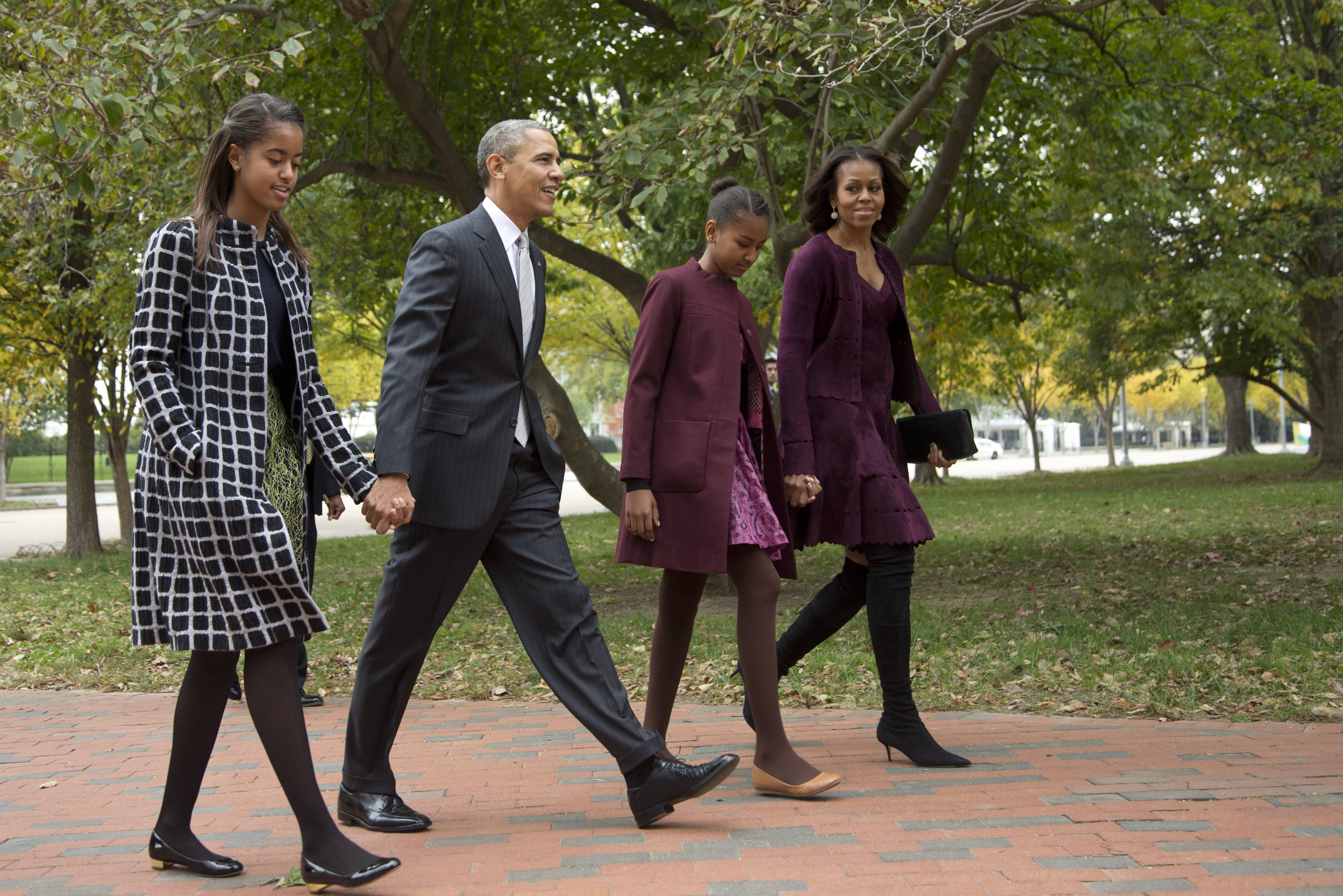 President Barack Obama, with first lady Michelle Obama and their daughters Malia, left, and Sasha, walk through Lafayette Park from the White House in Washington, to attend a church service Oct. 27, 2013. President Obama is practically weepy at the thought of his daughter Malia going off to college, a milestone many months away that is on his mind now.