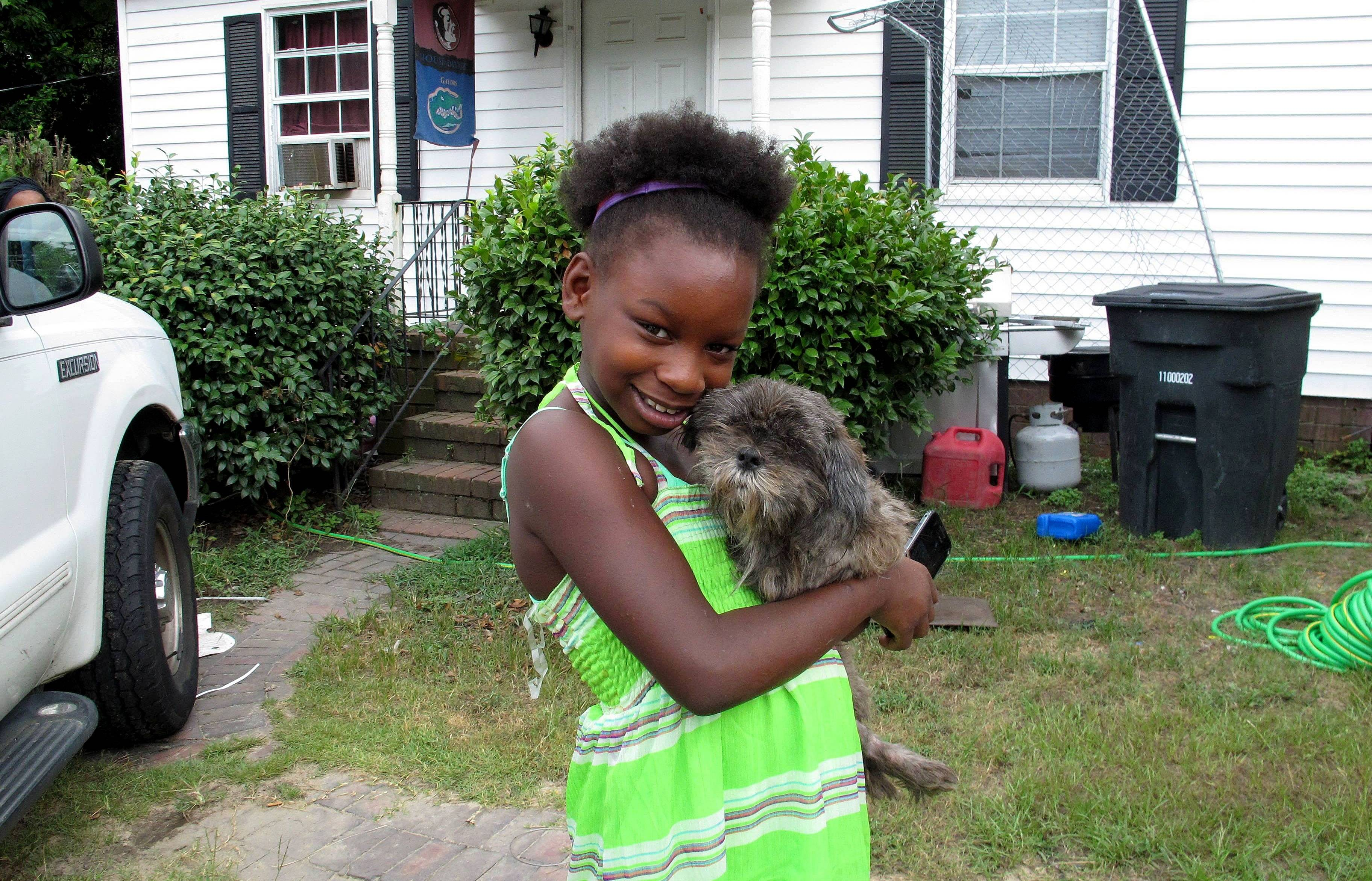 Regina Harrell, 9, holds her dog, Roscoe, outside her home, in North Augusta, S.C. Regina was taken from her home and her mother charged with a felony after her mother, Debra Harrell, left her alone to play at a nearby park while she worked at McDonald's.