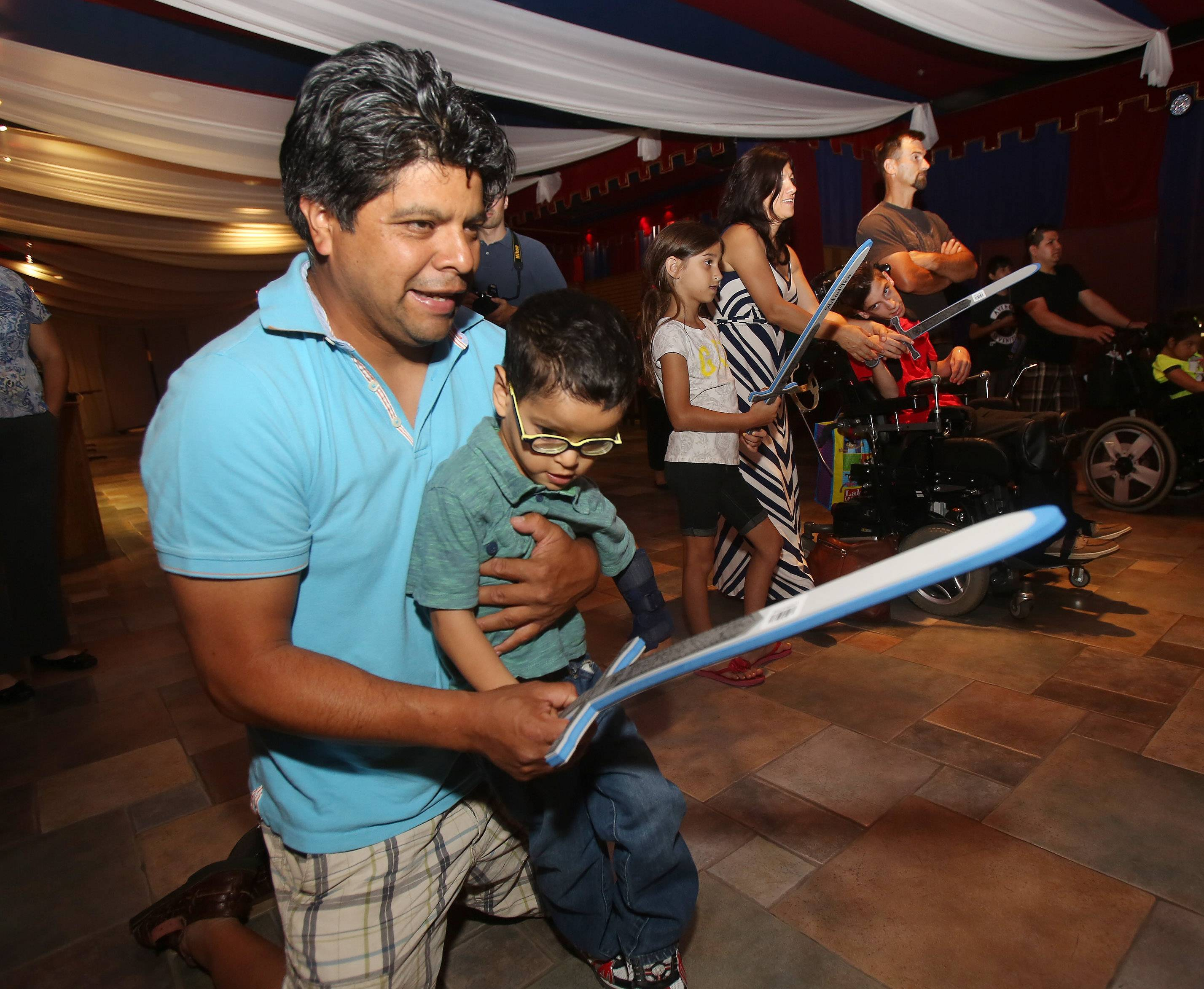 Temoc Aguilar of Chicago holds his son, Felipe, 5, while they practice with a sword as the group Variety Children's Charity teamed with Medieval Times in Schaumburg on Sunday to offer knight training to children with special needs.