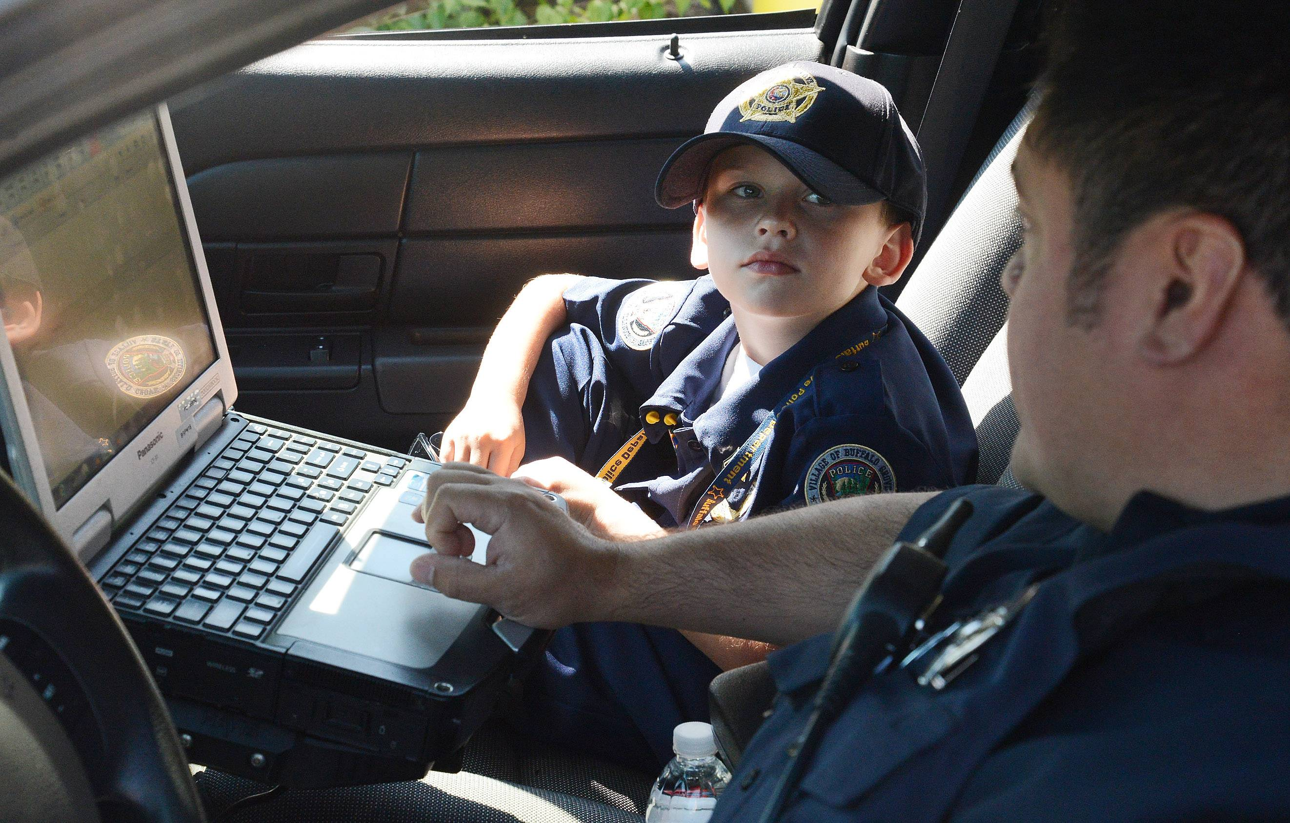 "7-year-old Adam Brodersen, of Palatine, is shown a squad car by Ofc. Mike Martin while being ""Cop-For-A-Day"" at the Buffalo Grove police department."