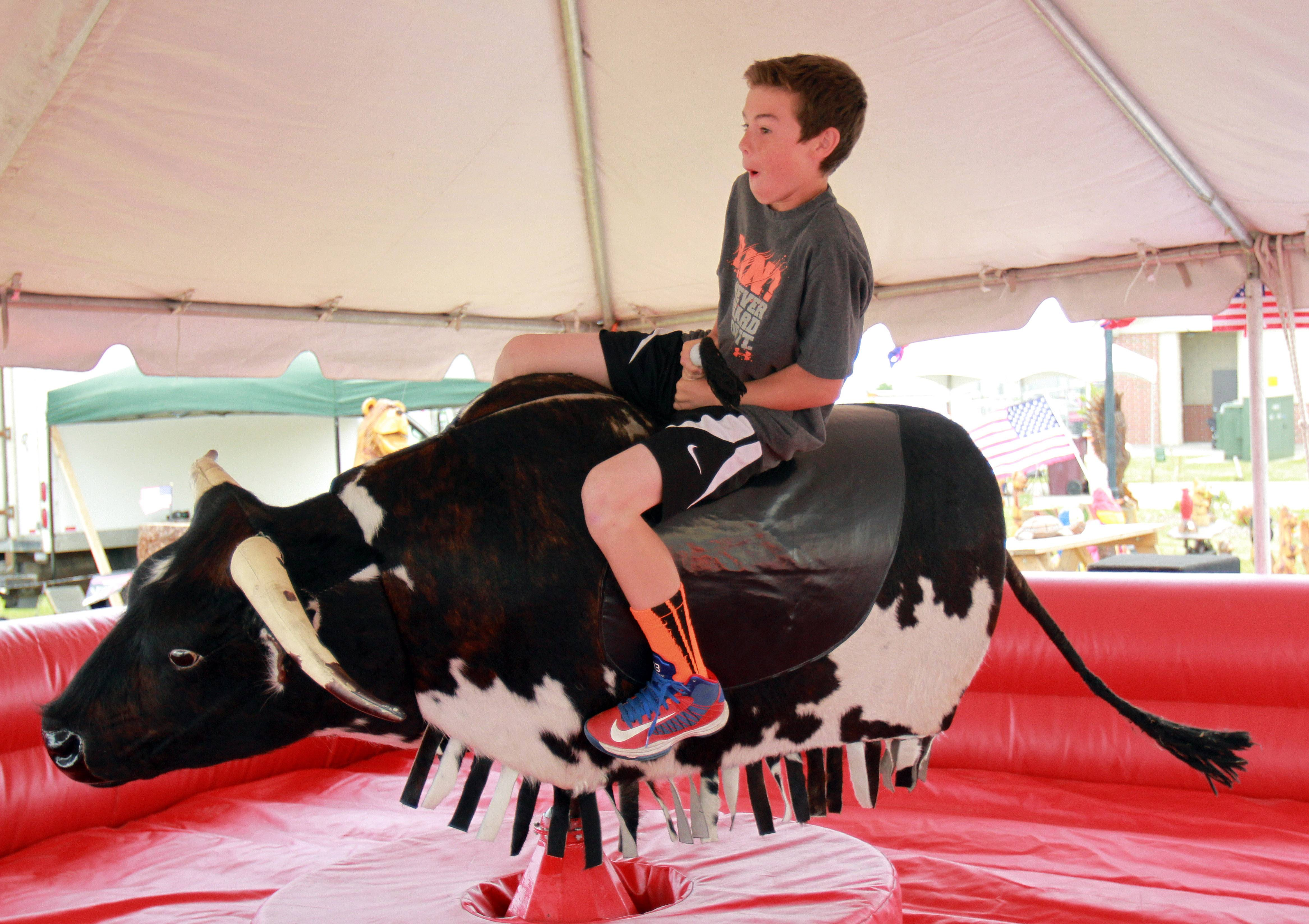 13-year-old Max Sanders, of Lindenhurst, rides a mechanical bull Friday at the Lake County Fair in Grayslake.