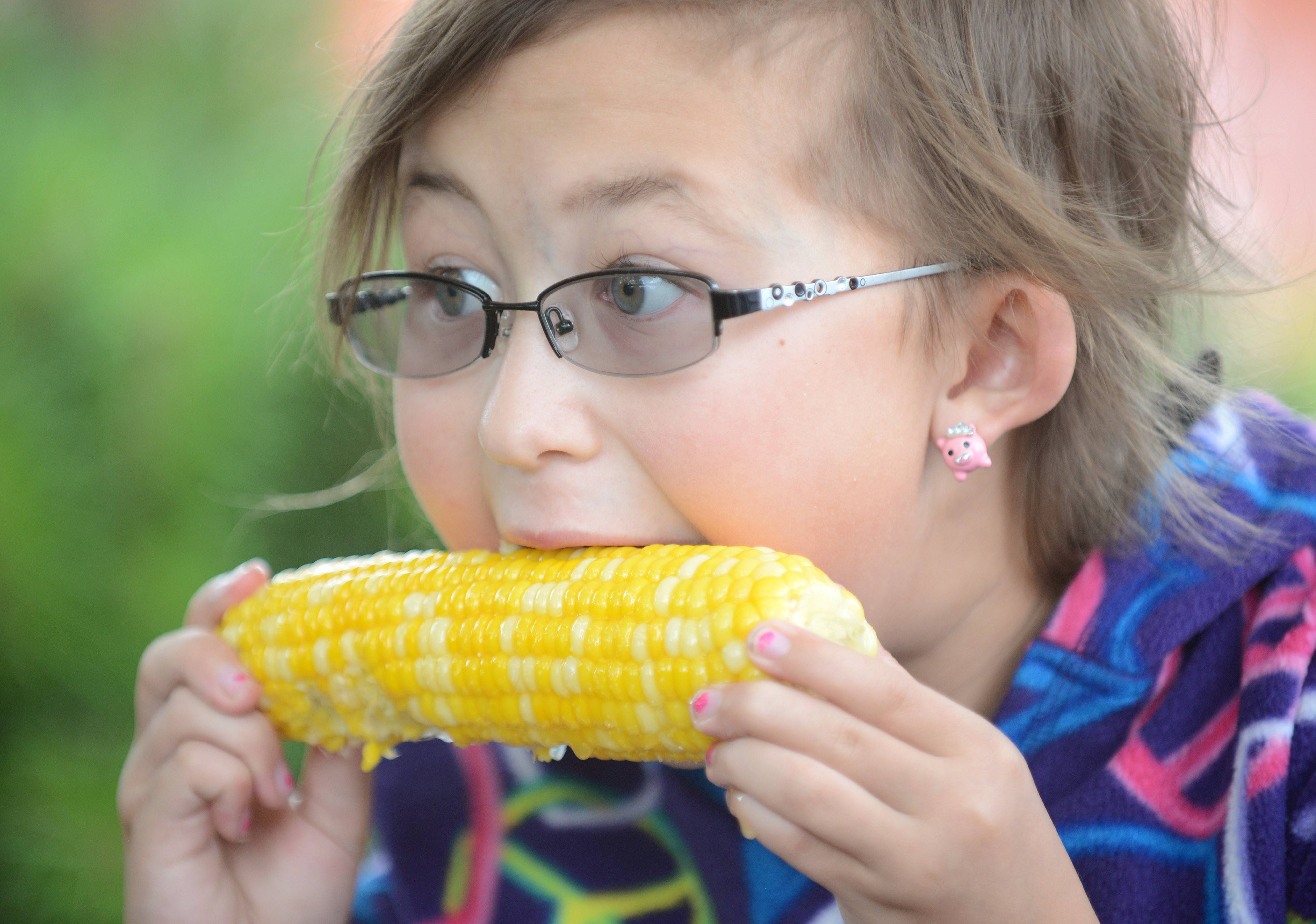 Caitlyn Grobe, 9, of Sugar Grove, chows down on an ear of corn at the Sugar Grove Corn Boil on Friday night. She has been coming every year since she was born.