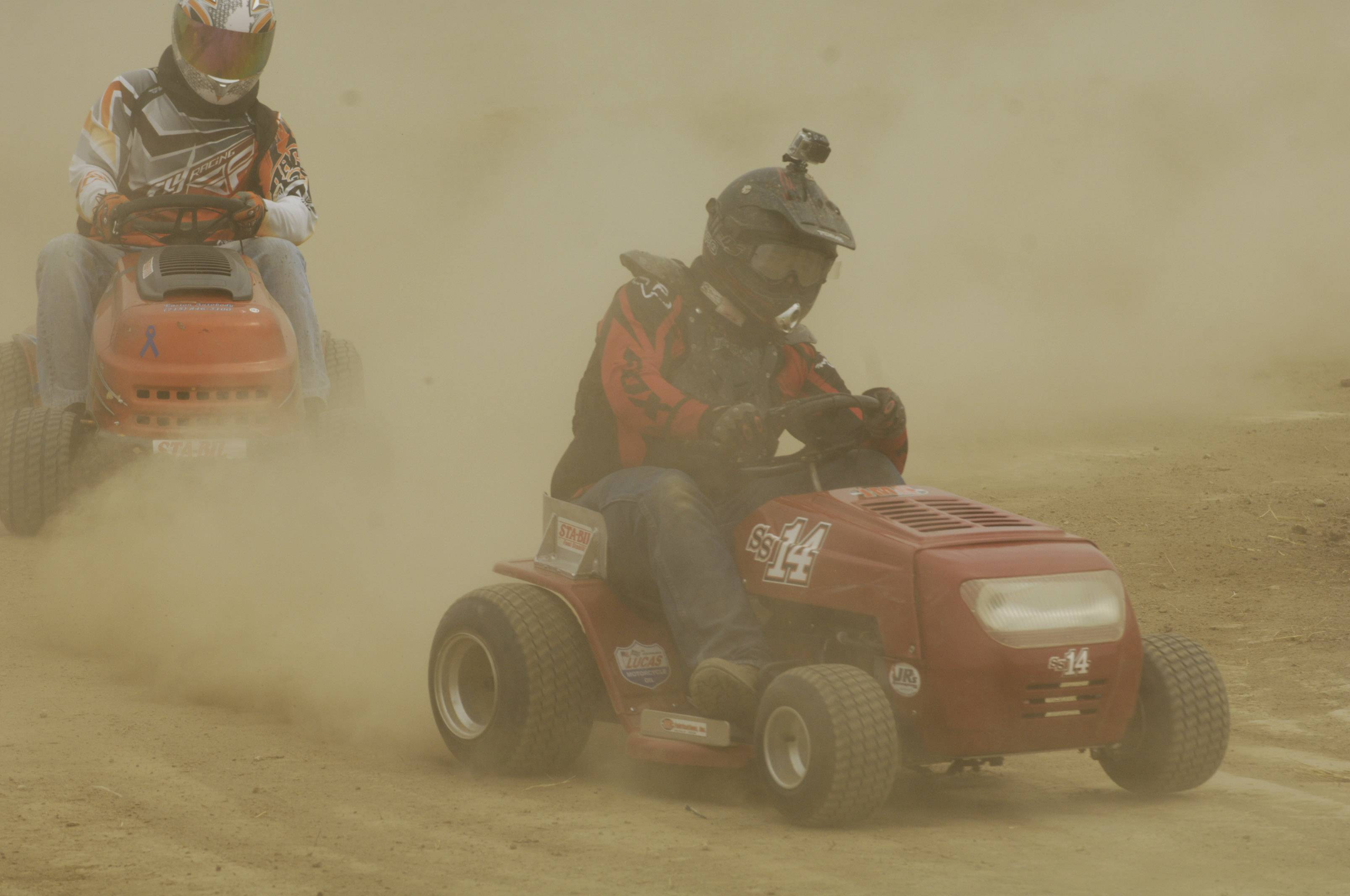 "Competitors kick up dust while negotiating a turn during the ""Mow Down Showdown"" lawn mower races at Lake County Fair in Grayslake Saturday."