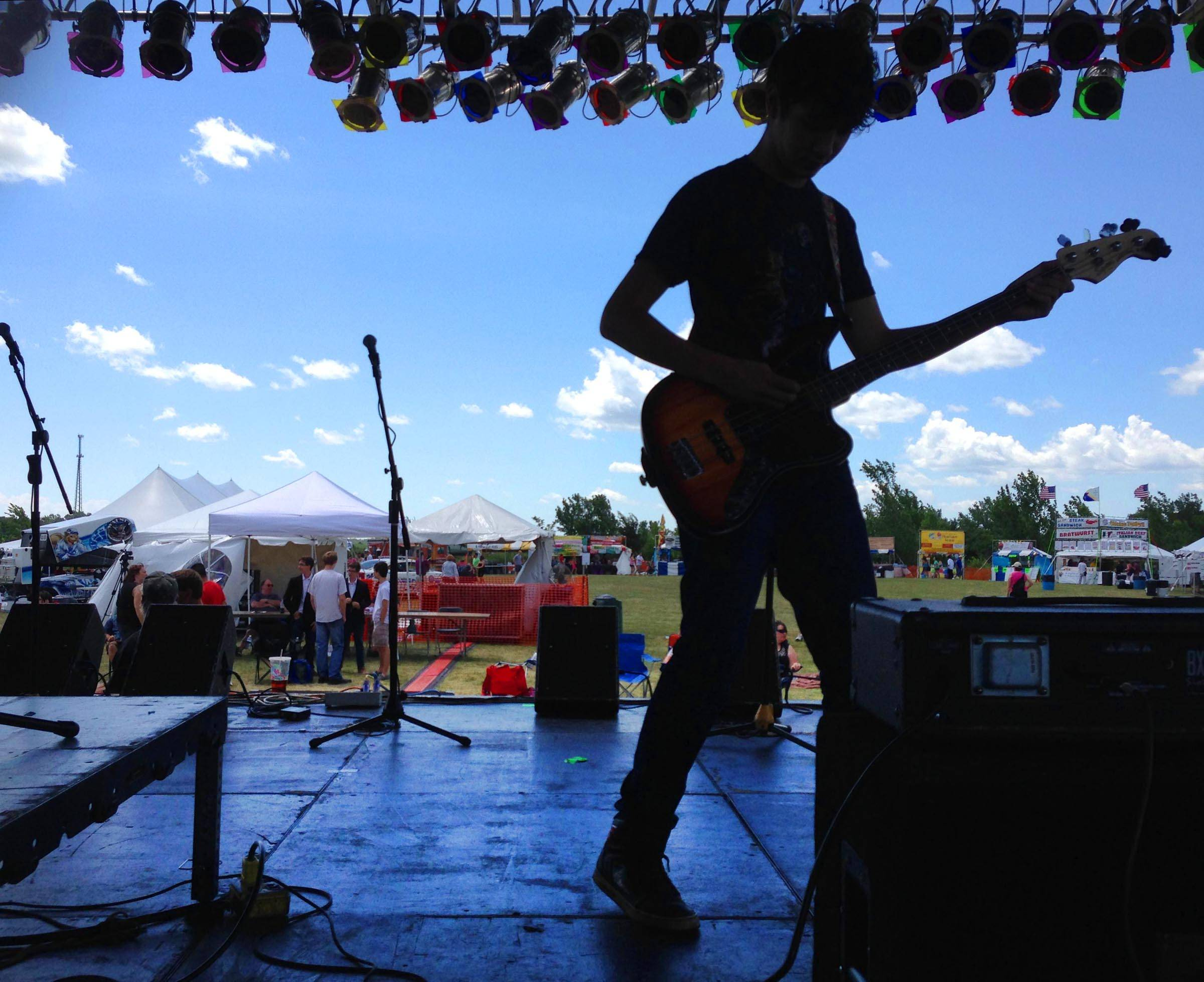 "Cesar Salceda, 18, tunes his bass guitar as his band ""The Choice"" prepares to take the stage Sunday at the Illinois Battle of the Bands regional competition at the Algonquin Founders Days Festival at Algonquin Lakes Park. The experimental indie rock band is from Chicago."