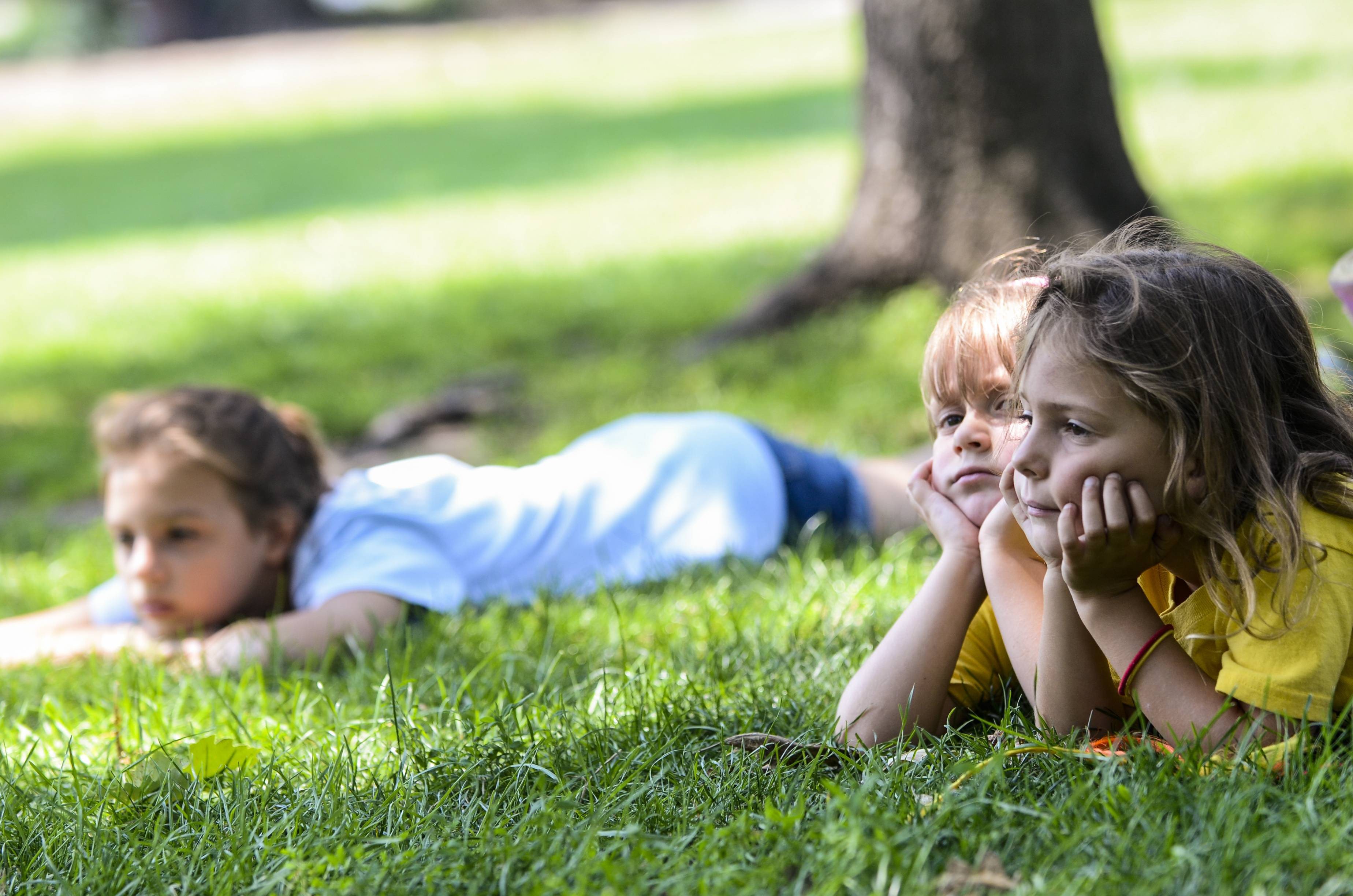 Ava Lilke, 12, Izabella Boniak, 5, and Kaelynn Woloszyk, 5, all of St. Charles, left to right, lie in the grass underneath a tree at Pottawatomie Park in St. Charles on Monday. The girls are part of the park district's summer camp, and the counselors tried to keep them cool by playing games underneath shade trees.