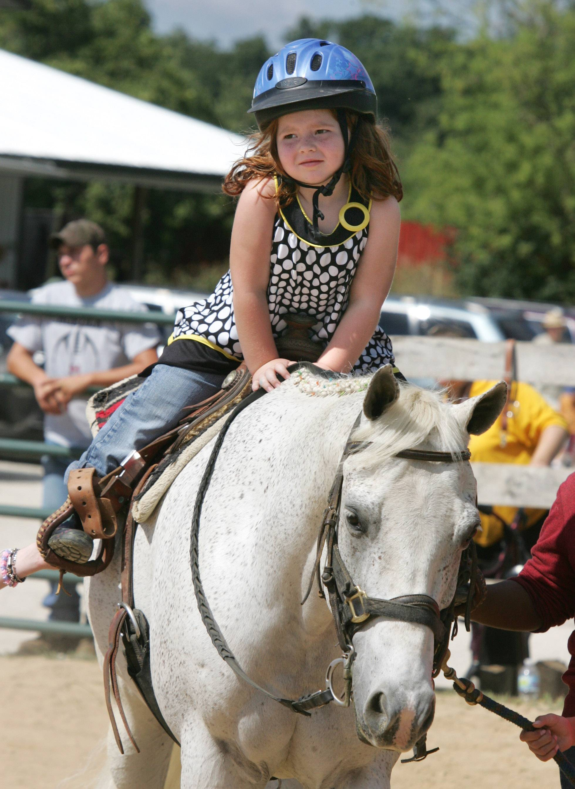 Four-year-old Emma Murray of Arlington Heights rides Cloud during the Family Summerfest and Participant Horse Show event hosted by Partners for Progress.