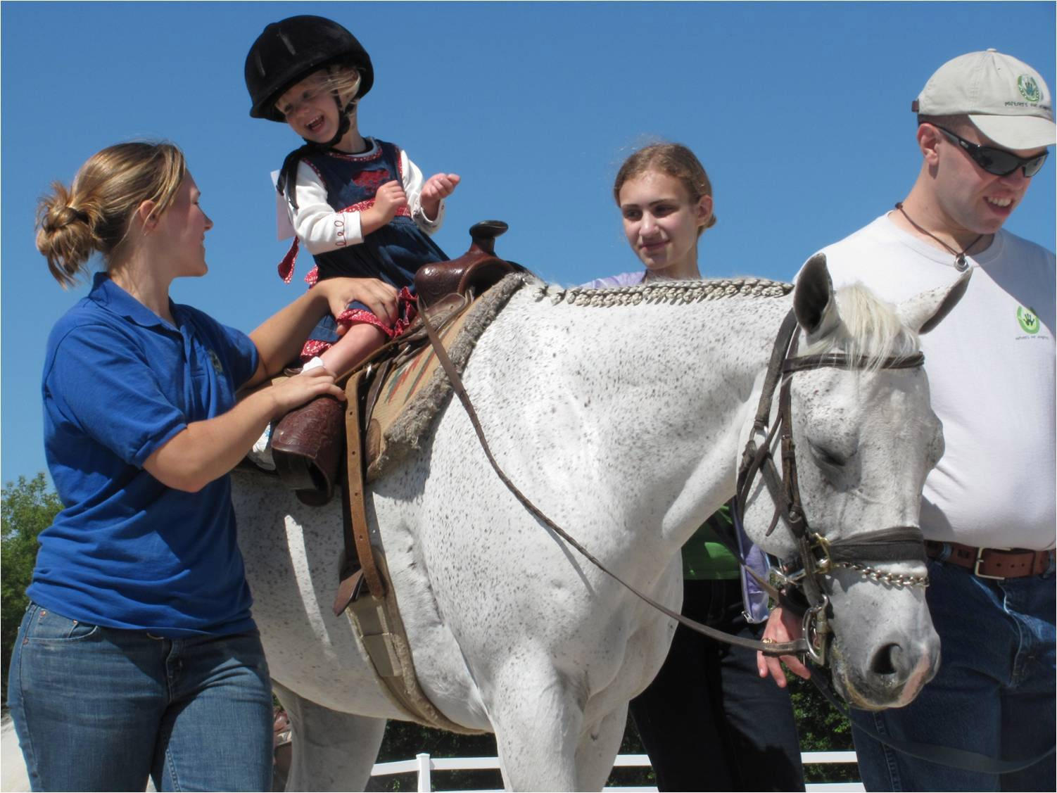 Volunteers work to make sure rider Brooke Smith, of Bristol, Wisconsin, has a safe and positive experience during her therapeutic riding session at Partners for Progress.