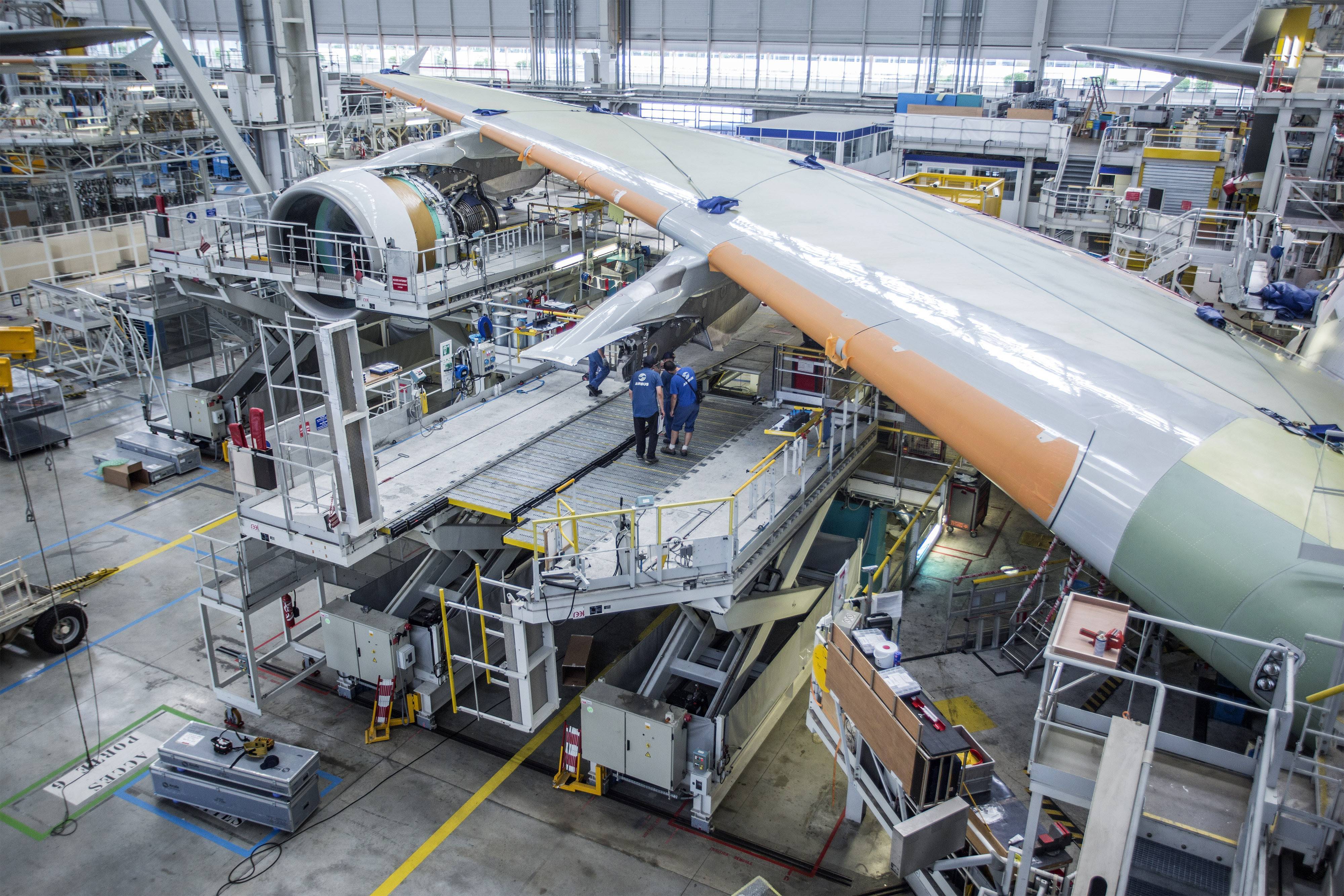 "Employees stand on a platform beneath the wing of a Airbus A380 aircraft on the assembly line at the Airbus Group NV factory in Toulouse, France. Chicago-based Boeing competitor Airbus Group NV said it's closely monitoring the financial health of customers for the flagship A380 and acknowledged that not all superjumbos on order will get built after it pulled a purchase accord with a Japanese carrier. ""Without referring to any specific airline, I can assure you that we have cases where airlines are in the order backlog but not in the production plan,"" Chief Executive Officer Tom Enders said today on a conference call to discuss earnings. ""We are watching the situation carefully, and know about the strengths and weaknesses of customers."""
