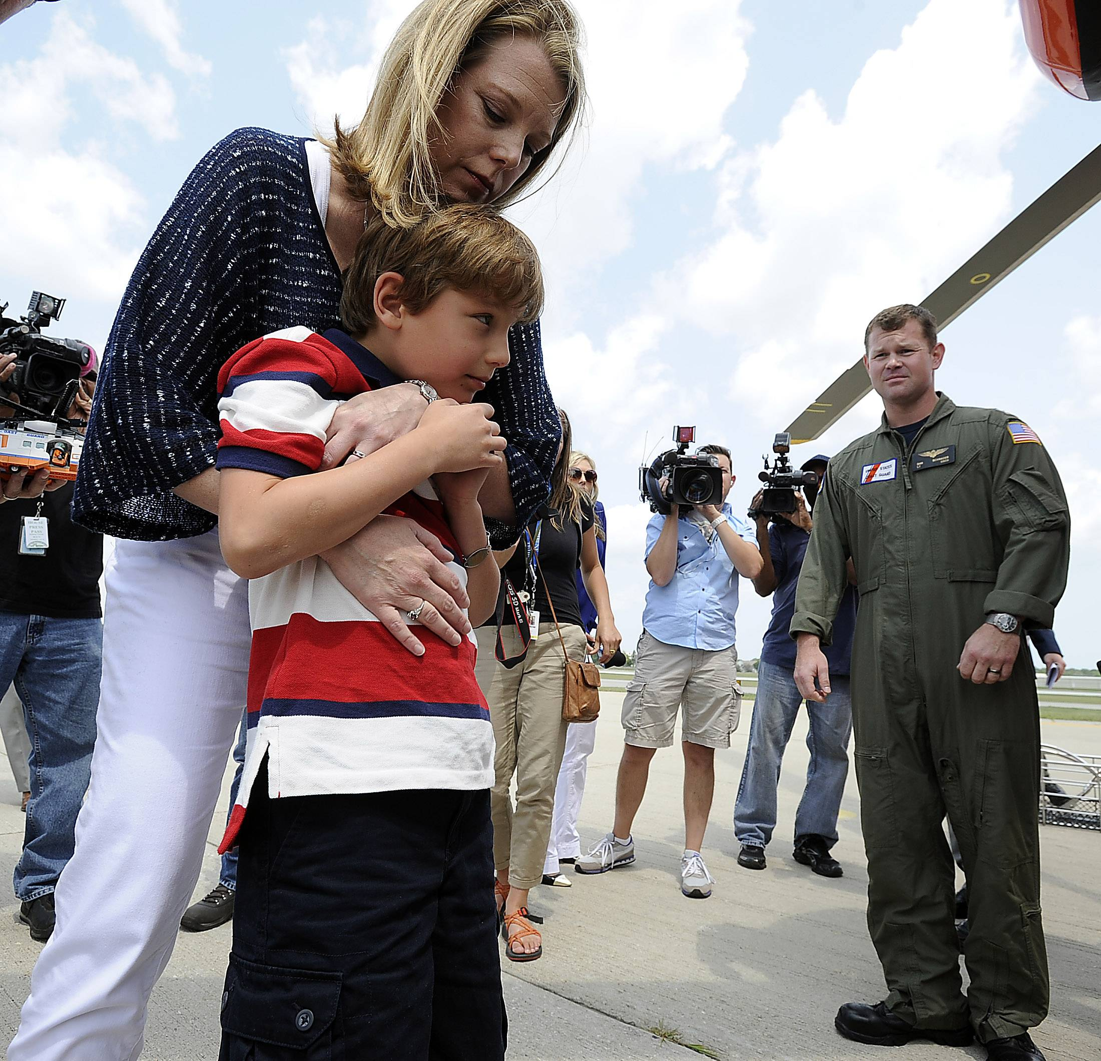 Tommy Alter, 9, of Highland Park is hugged by his mother, Leslie, during a reunion with his Coast Guard rescuers Tuesday. Nearby is Lt. Dan Schrader, the pilot of the mission.