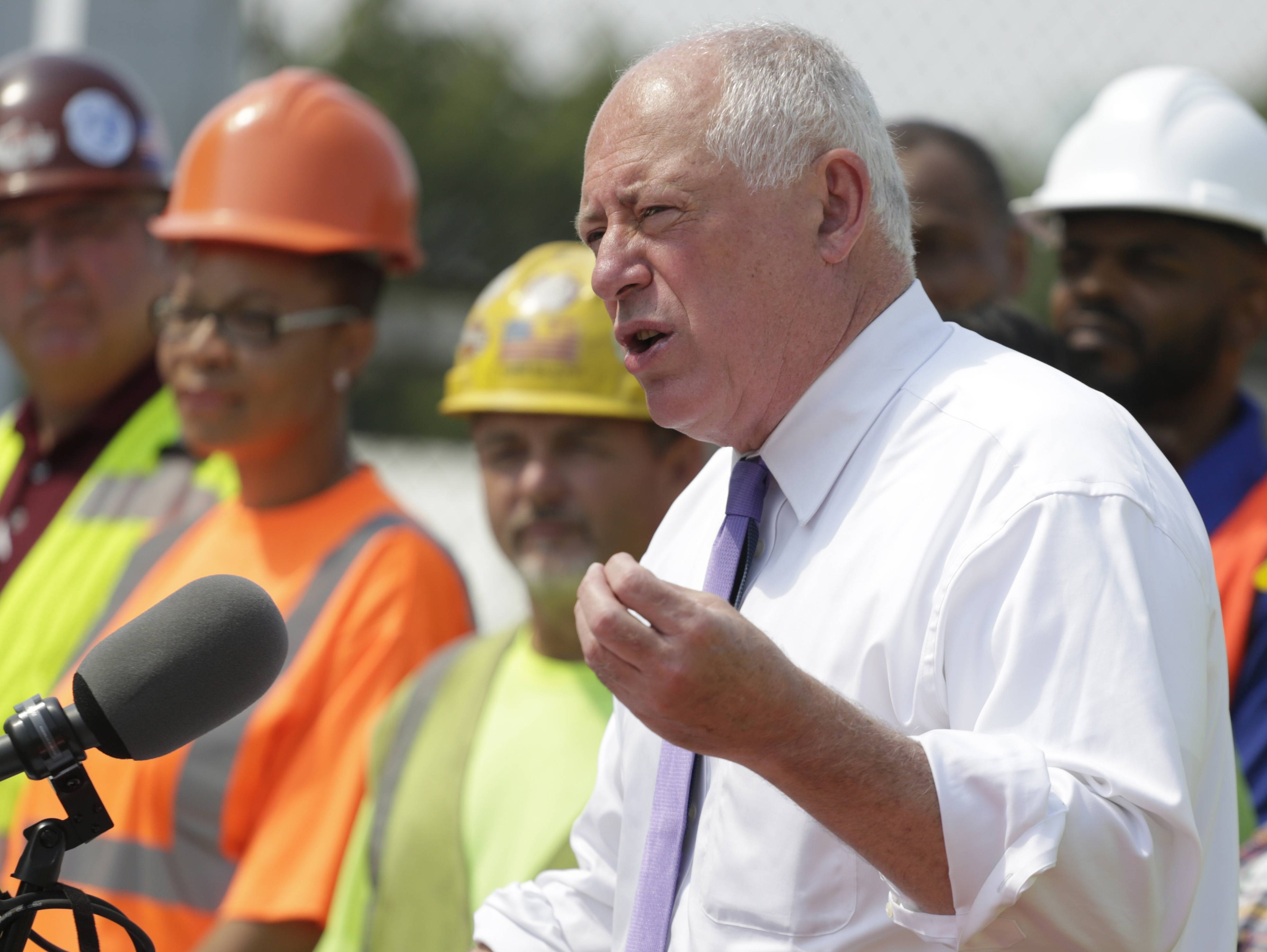 "In this July 22, 2014, photo in Chicago, Illinois Gov. Pat Quinn, surrounded by workers, speaks during a bill signing ceremony. The candidates for Illinois governor have ridiculed each other's plans for the state budget in recent weeks, with Republican Bruce Rauner accusing Gov. Quinn of leading a ""tax-happy, fee-happy state,"" and the Chicago Democrat countering that Rauner's plan to cut taxes is a dishonest, ""flim flam approach"" that will leave an $8.5 billion budget hole. But a closer look at the state's books and the two candidates' plans shows both sides are playing a little fast and loose with the numbers. (AP Photo/M. Spencer Green)"