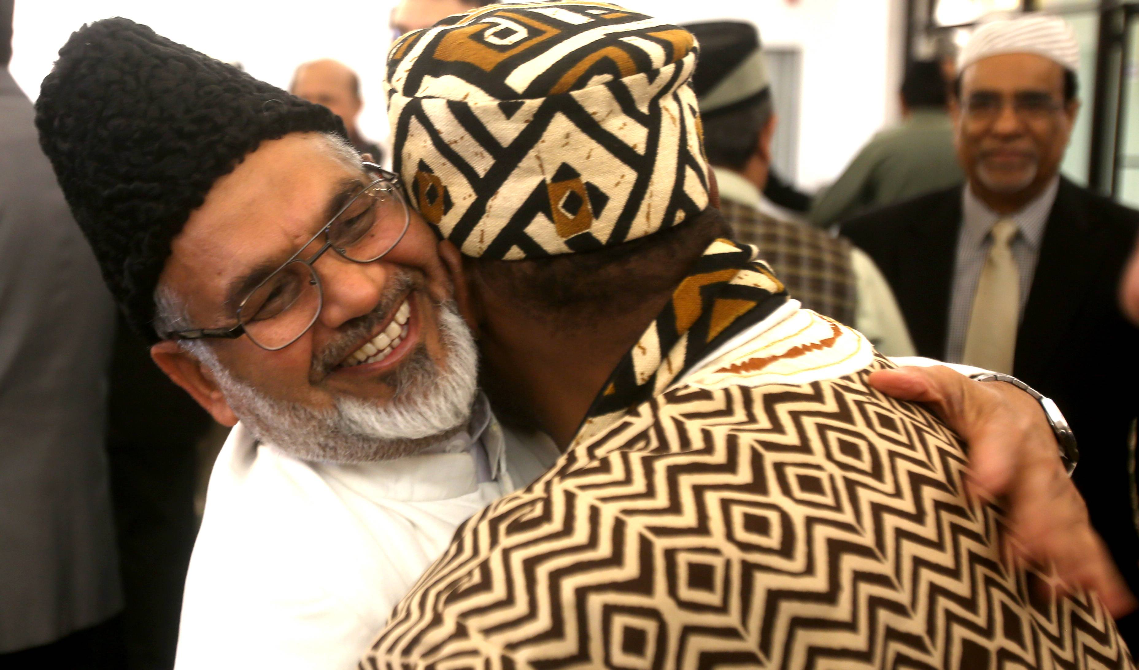 Following his sermon, Imam Shamshad Nasir greets fellow worshippers as the Ahmadiyya Muslim Community celebrates the end of Ramadan at its Glen Ellyn mosque.